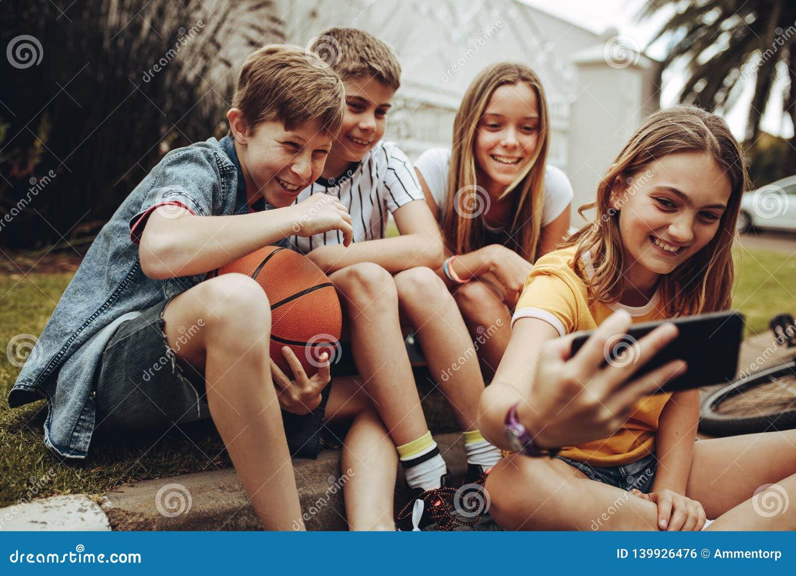 Niños que toman un selfie que se sienta al aire libre