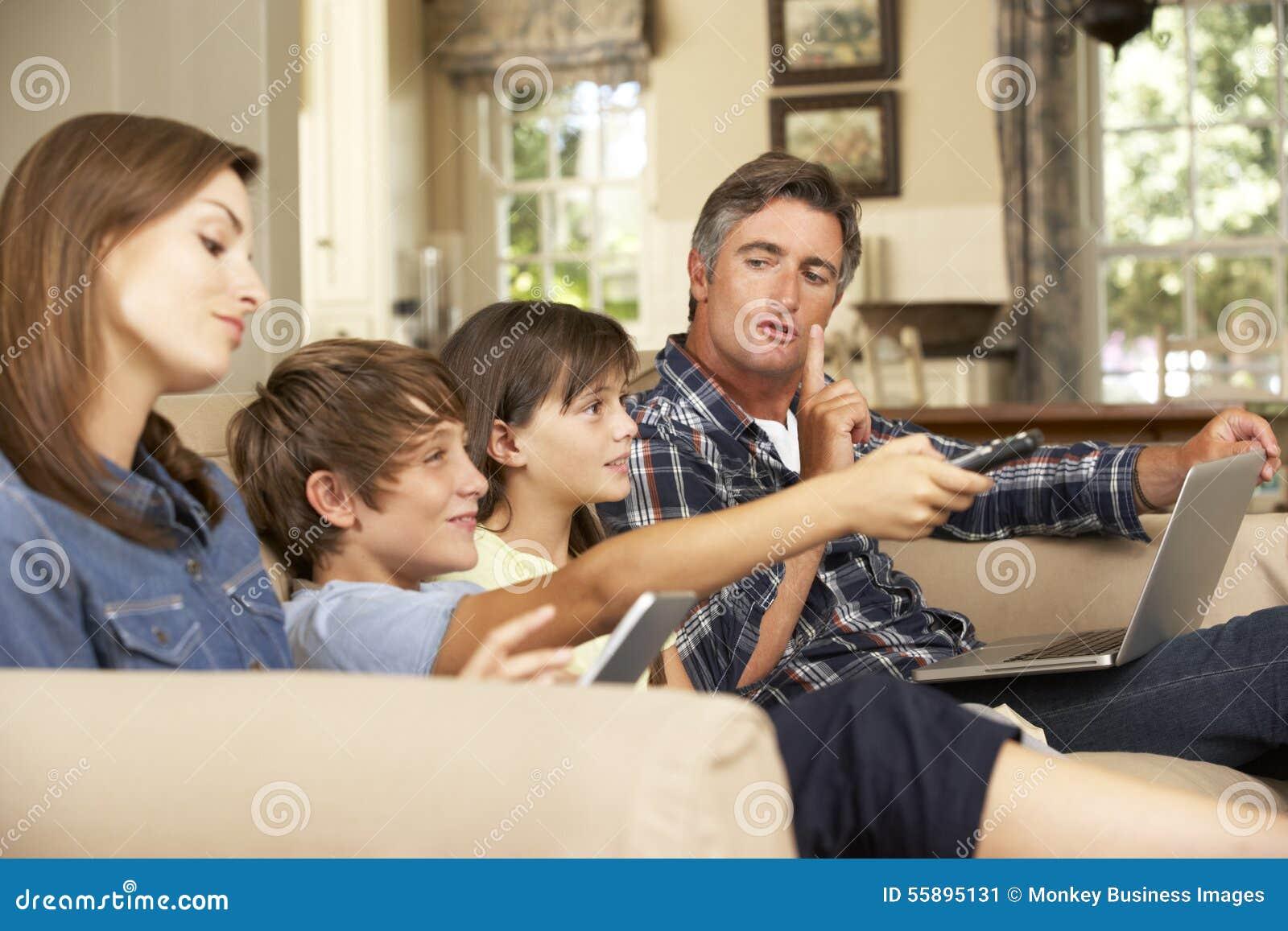 Niños que ven la TV mientras que los padres utilizan el ordenador portátil y la tableta en casa