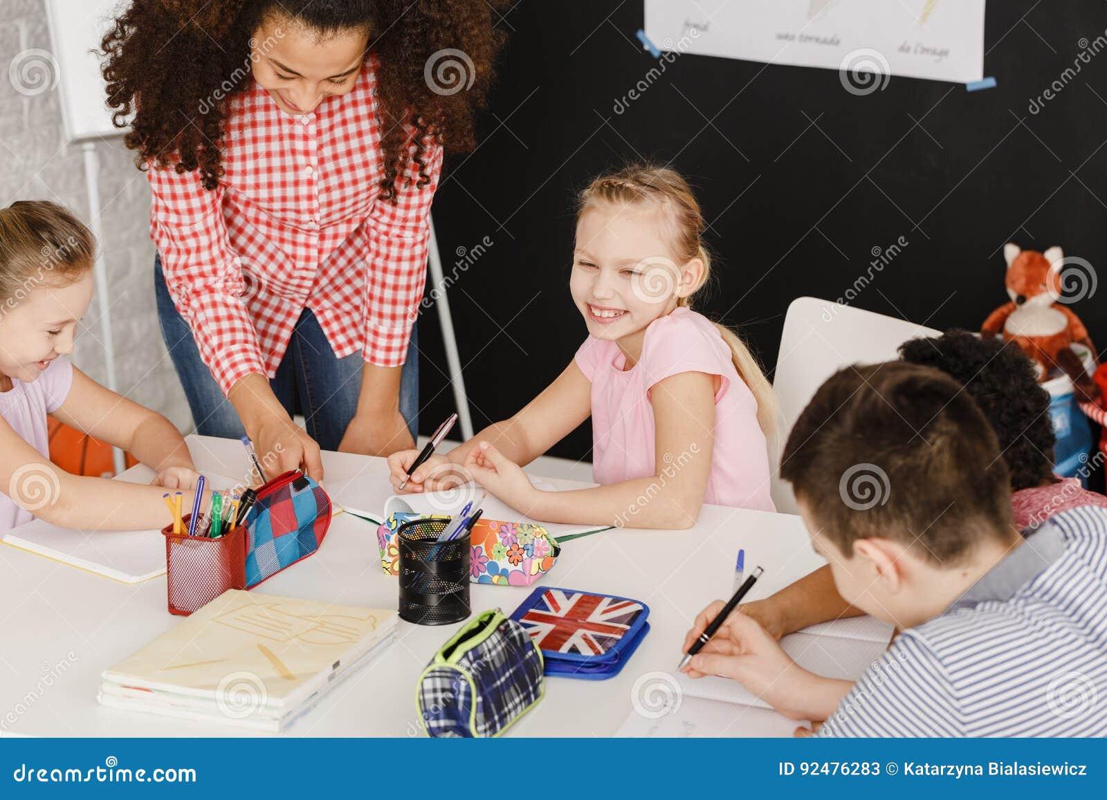 Niños sonrientes y profesor de sexo femenino