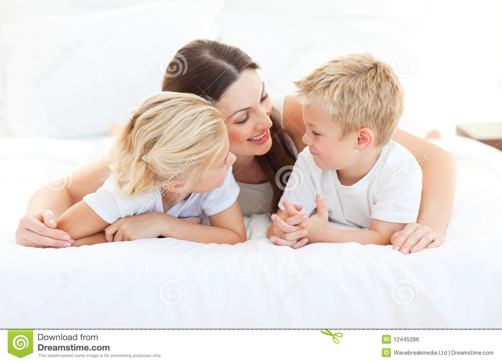 Niños y su mama que discuten la mentira en una cama