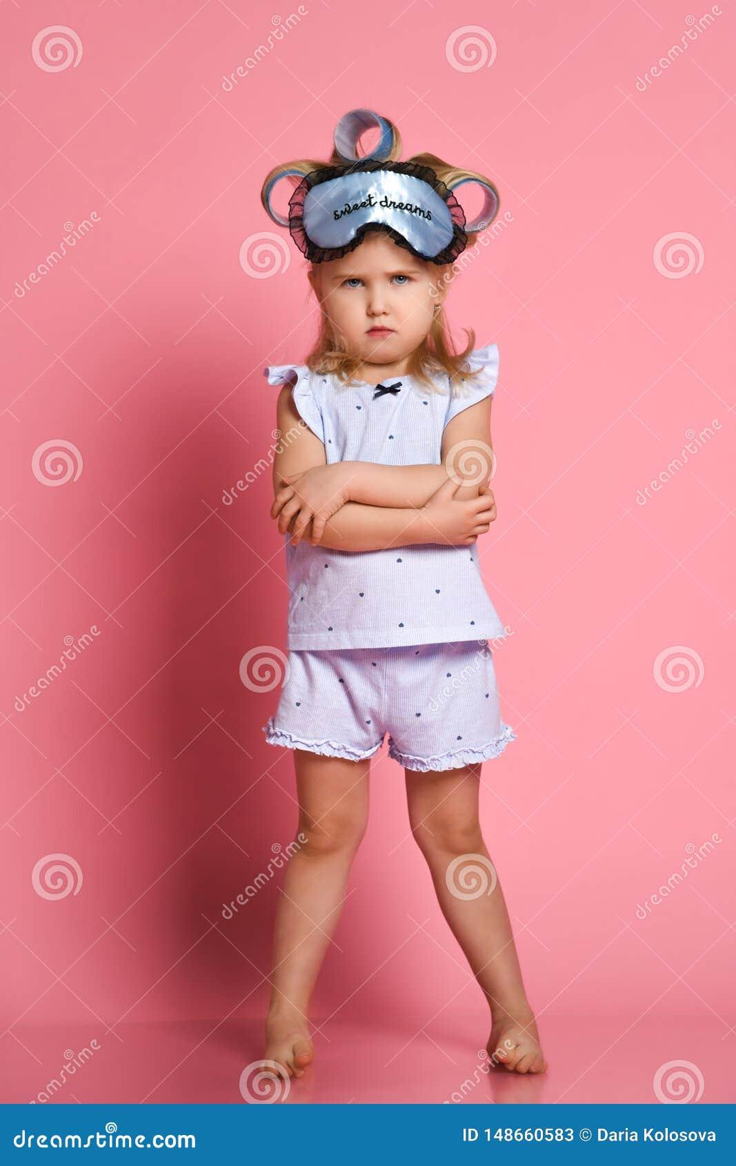 Ni?a enojada en pijamas y una m?scara del sue?o, ella dobl? sus brazos en una actitud en su pecho y frunci? el ce?o en la c?mara