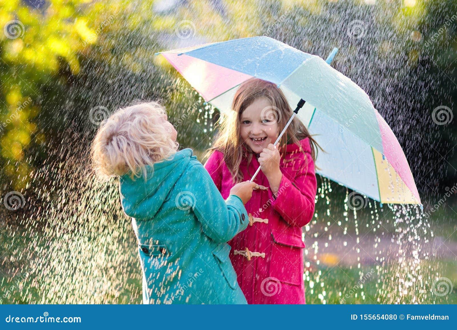 Ni?os con el paraguas que juega en lluvia de la ducha del oto?o