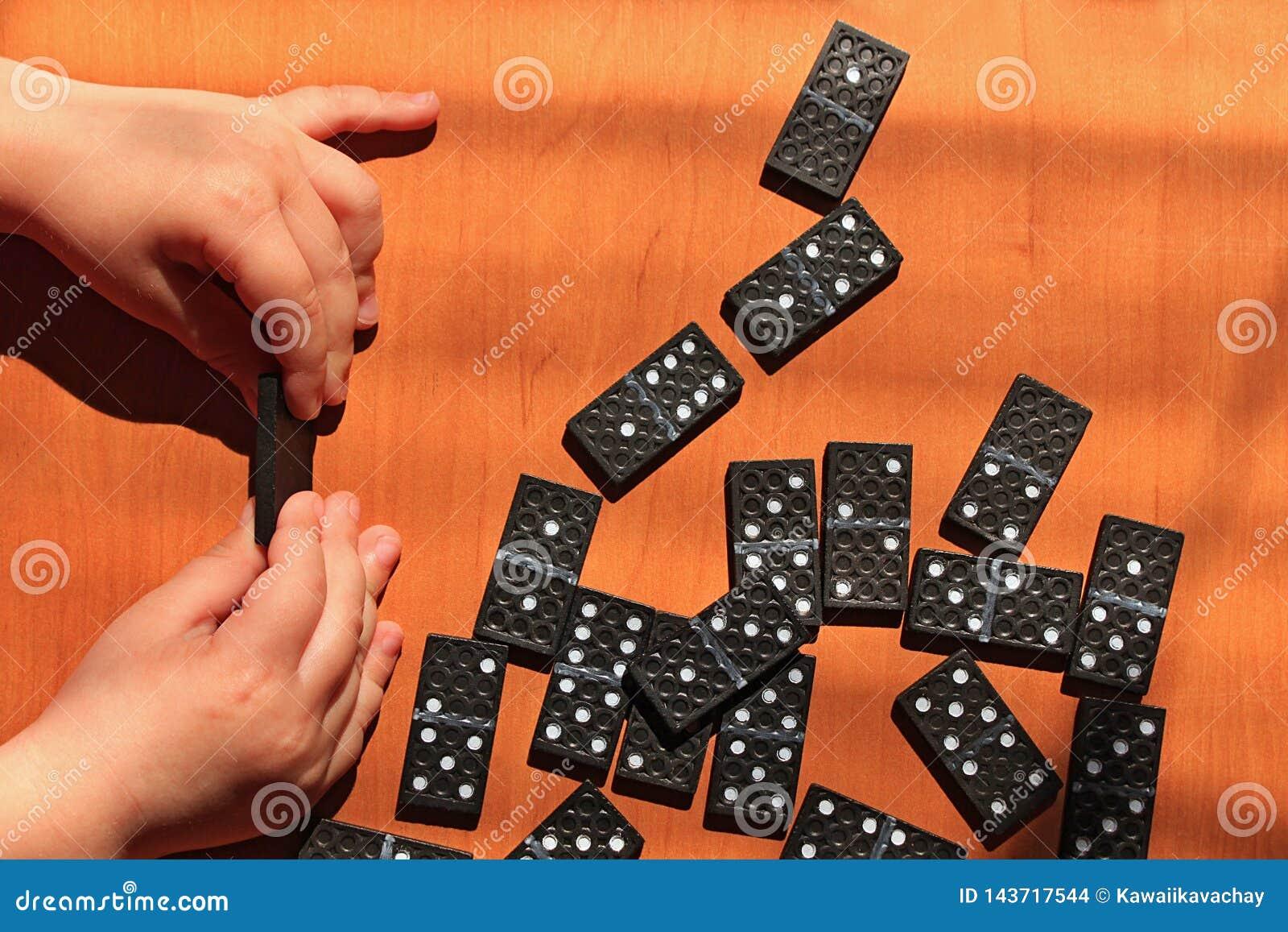 Ni?os de ense?anza para jugar al juego de los domin?s en un fondo de madera