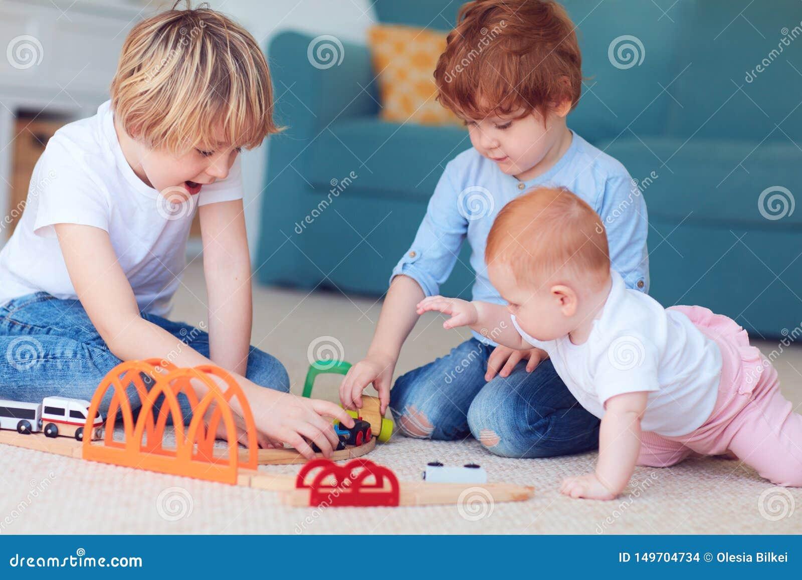 Ni?os lindos, hermanos que juegan los juguetes juntos en la alfombra en casa