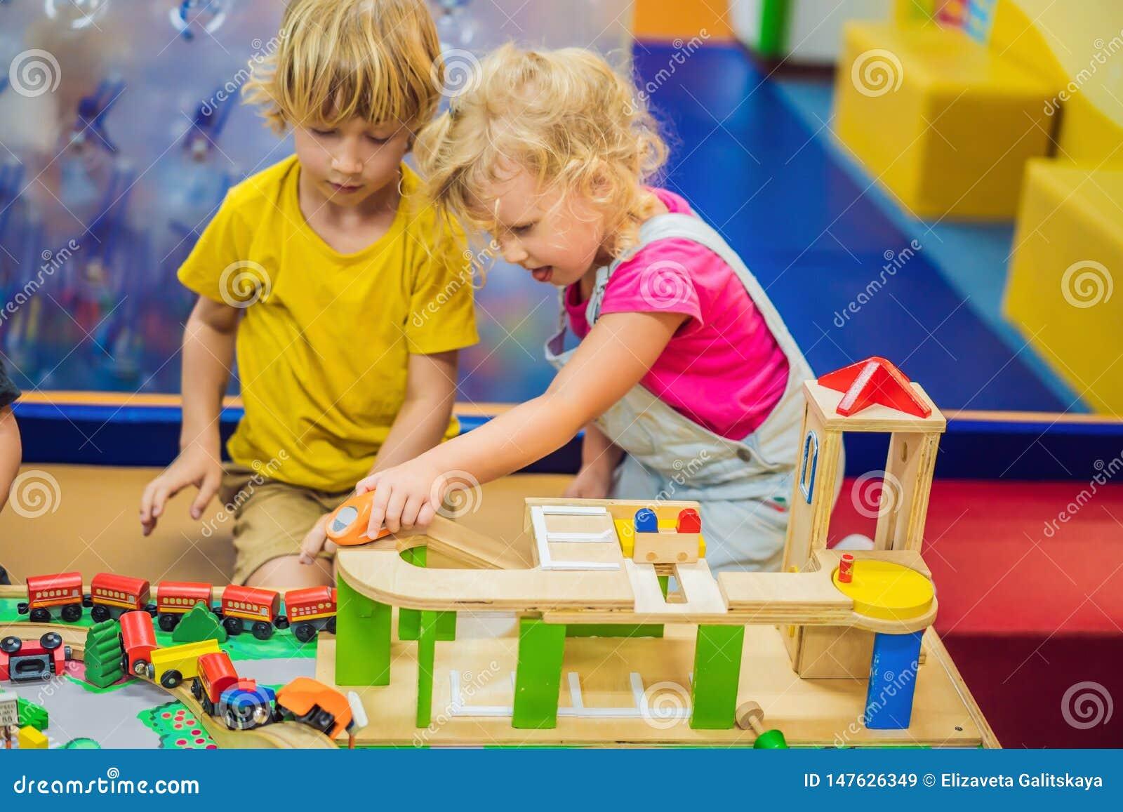 Ni?os que juegan con el tren de madera El ni?o y el beb? del ni?o juegan con los bloques, los trenes y los coches Juguetes educat