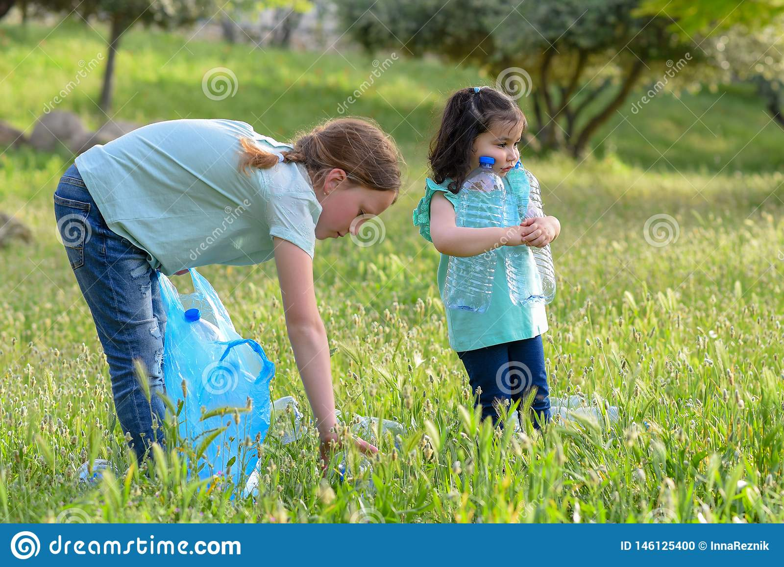 Ni?os que limpian en parque Ni?os voluntarios con un bolso de basura que limpia la litera, poniendo la botella pl?stica en el rec