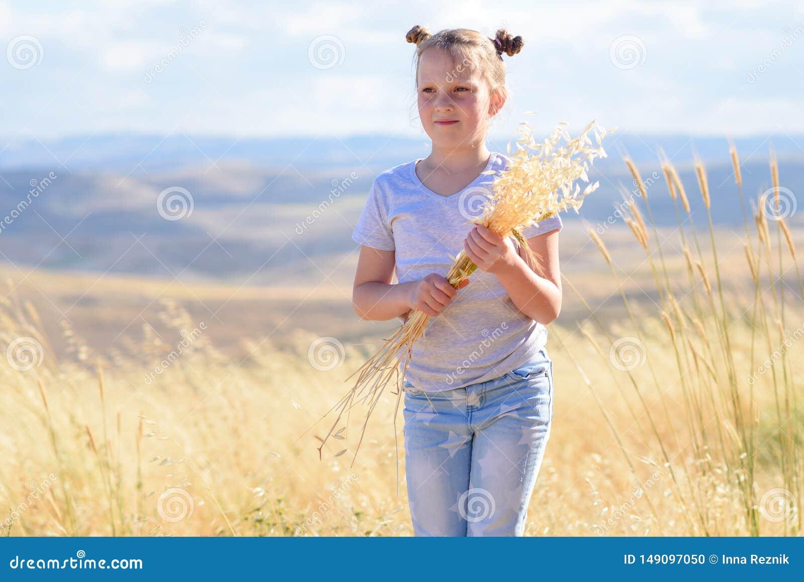 Ni?a rubia que lleva a cabo puntos del trigo y de los o?dos de la avena en campo de oro de la cosecha