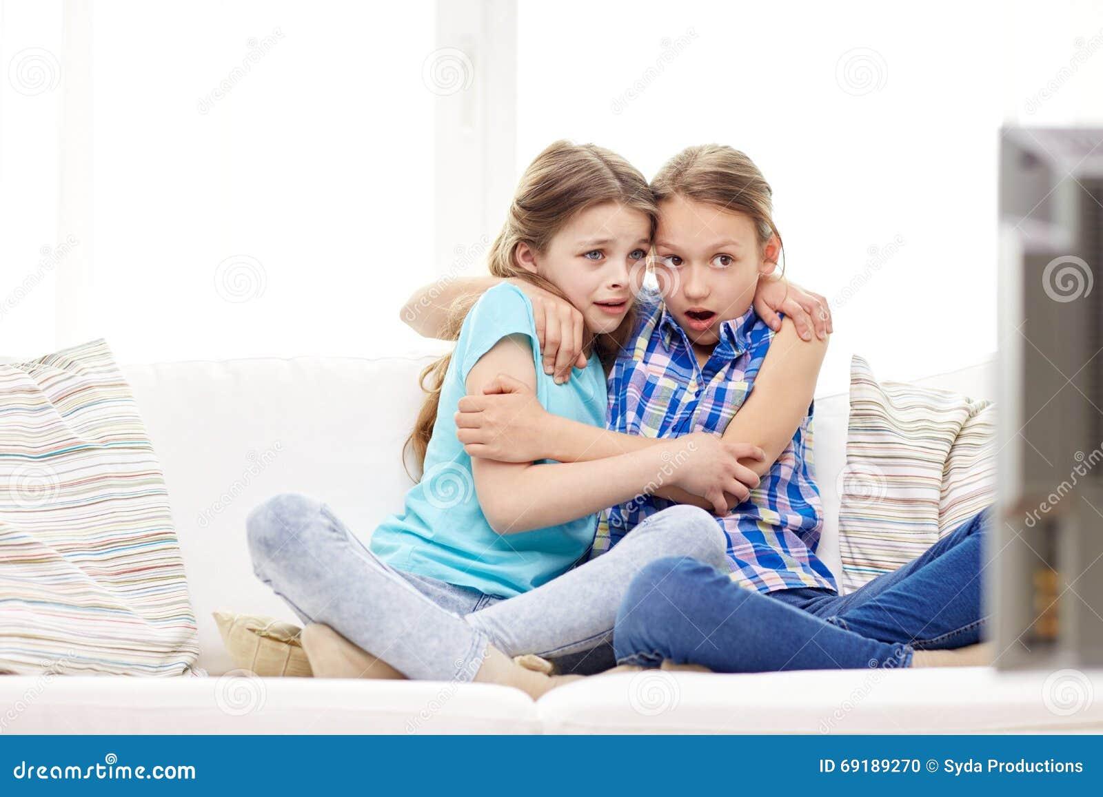 Ni as asustadas que miran horror en la tv en casa foto de - Television en casa ...