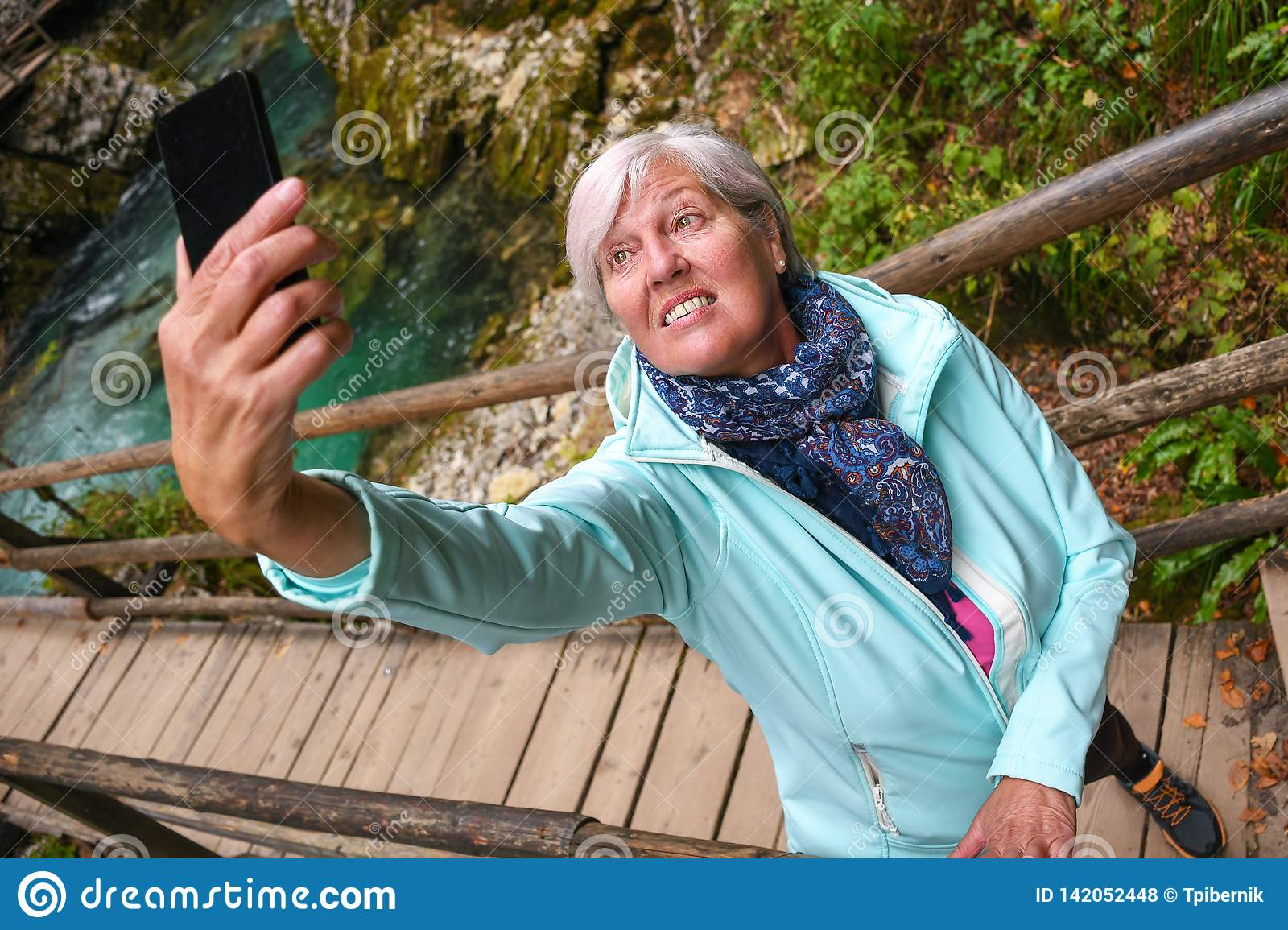 Nice attractive elderly mature woman with shiny grey hair taking photos and selfies outdoor