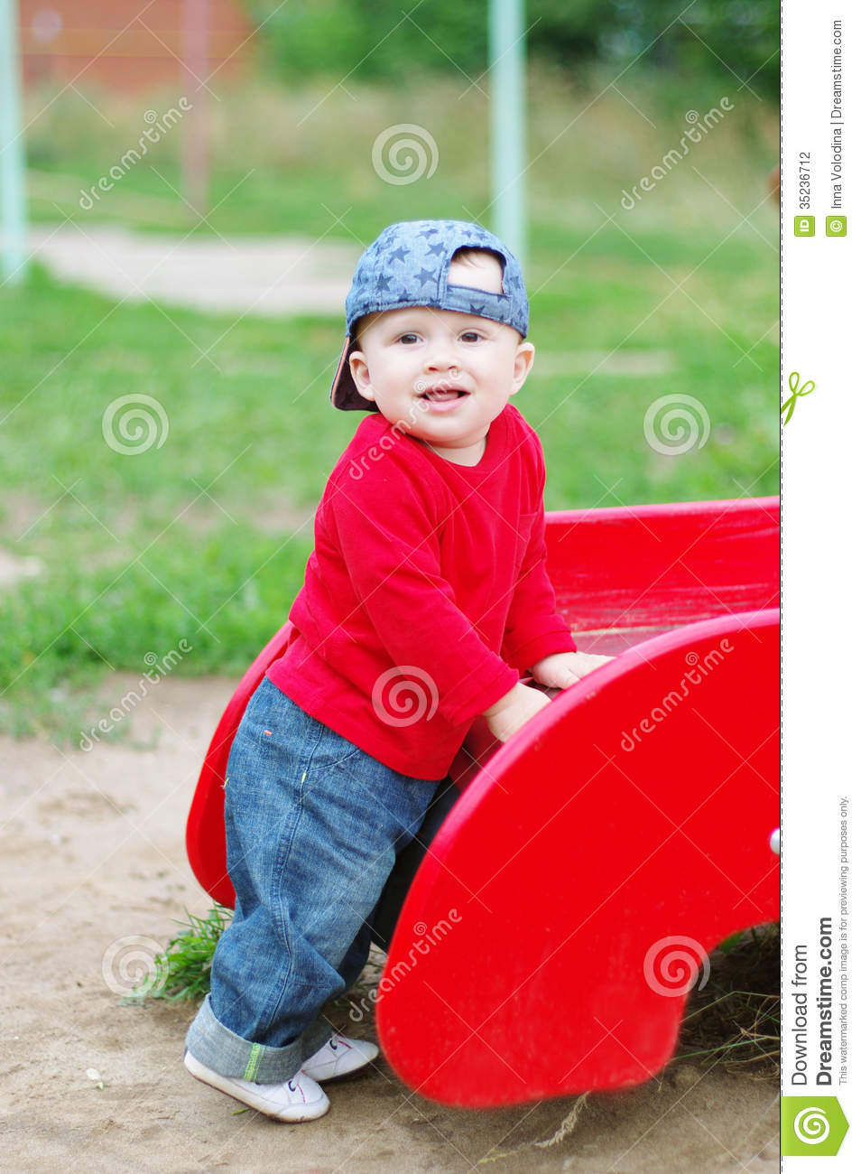 Nice Baby Boy Age Of 10 Months On Playground In Summer