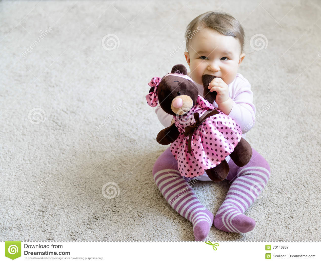 nice baby girl bites the paw of the toy bear stock image - image of