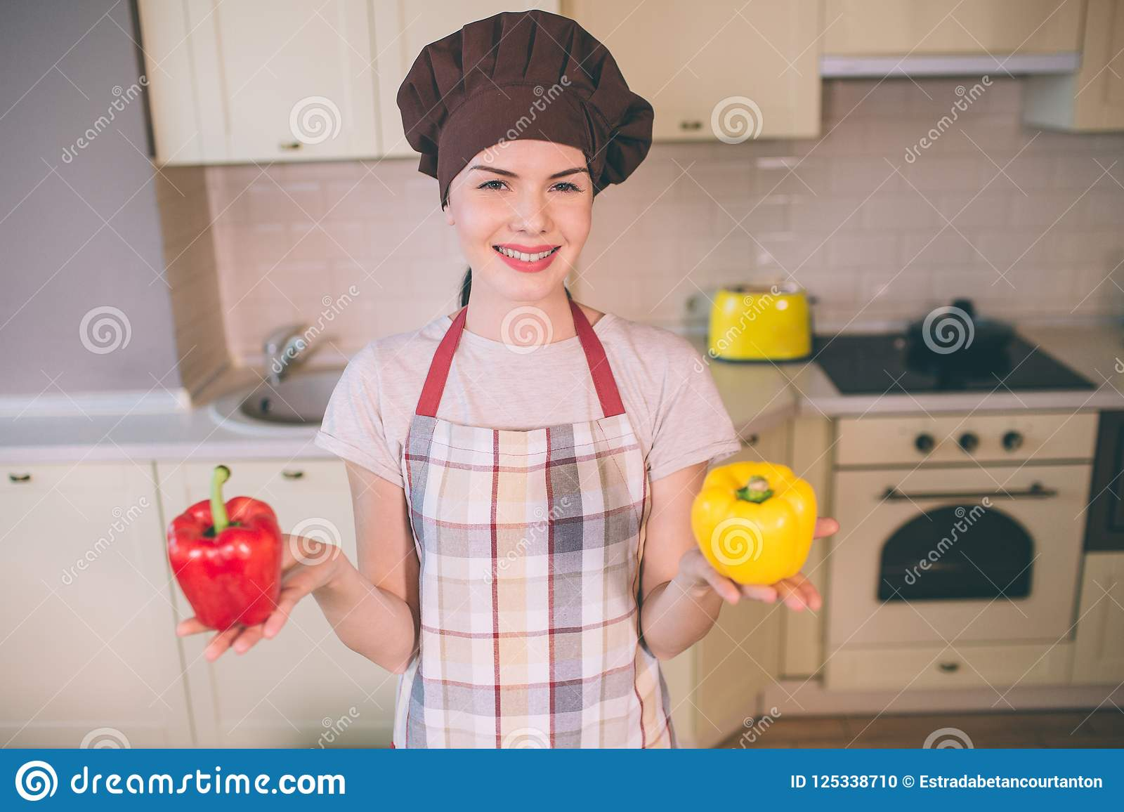 Nice And Beautiful Woman Stands In Kitchen She Holds Red And Yellow Peppers Girl