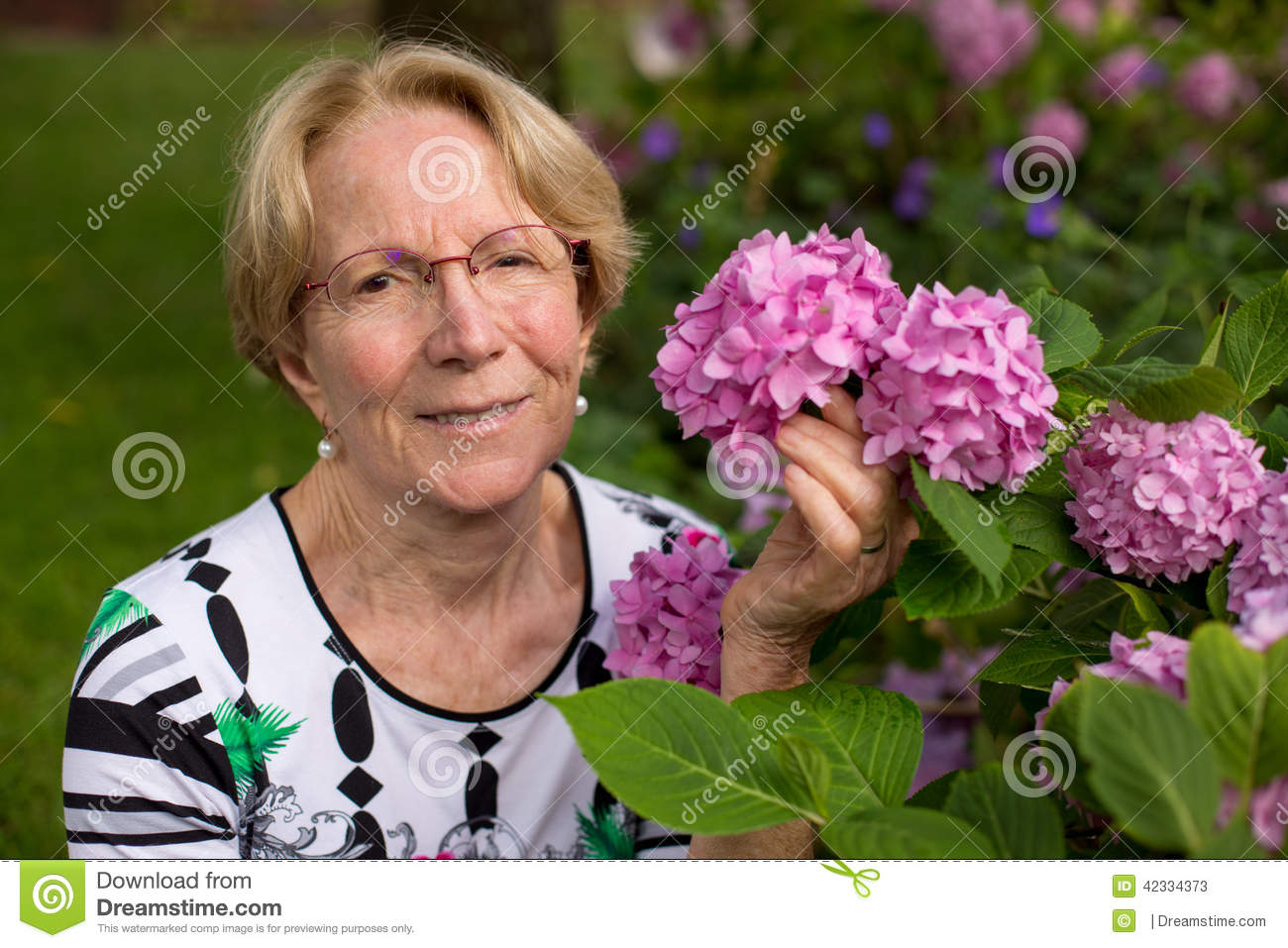 A Nice Elderly Woman Is Posing In Front Of Beautiful Pink