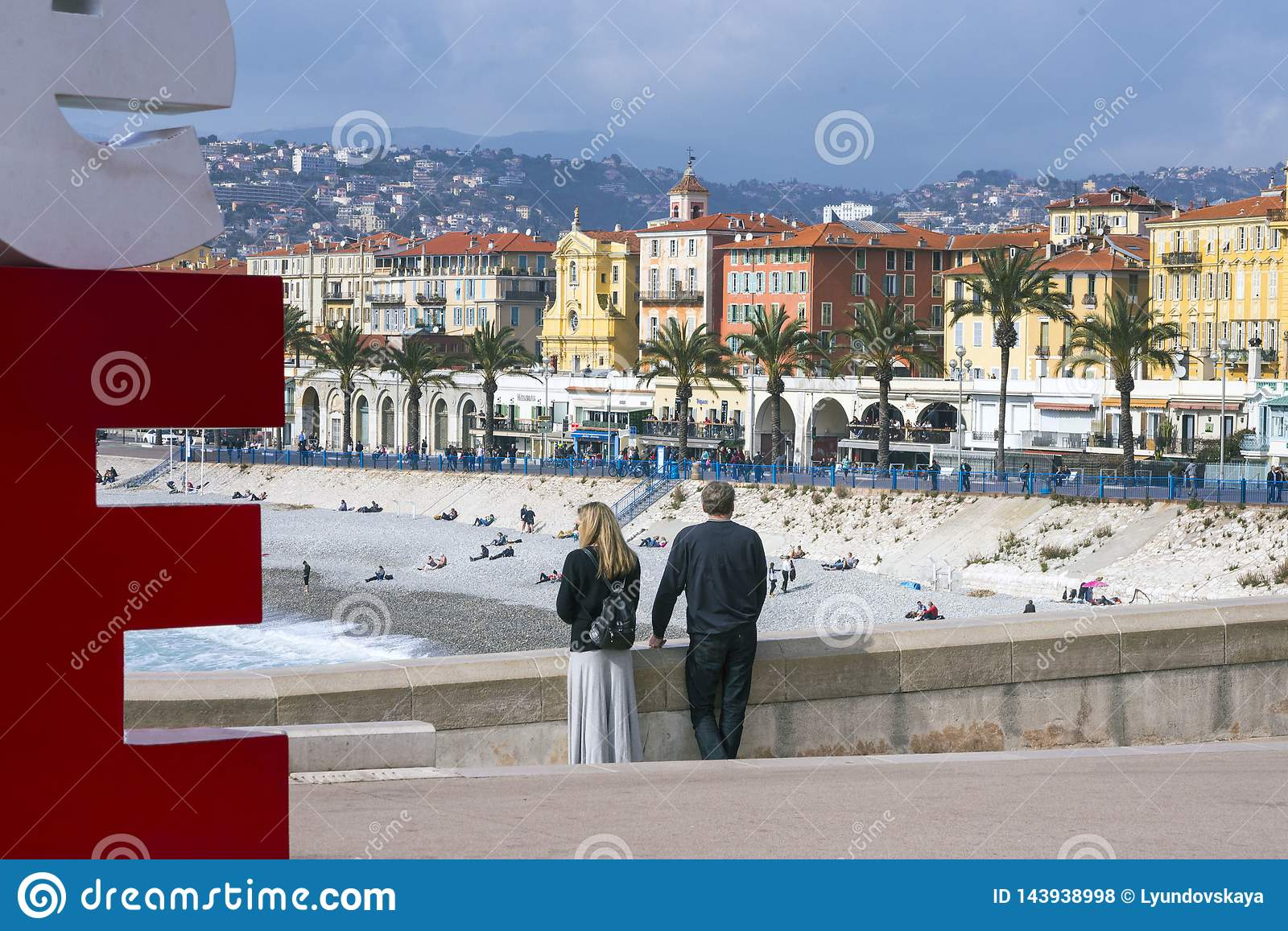 Nice, France, March 2019. Panorama. Azure sea, waves, English promenade and people resting. Young couple: a man and a woman look