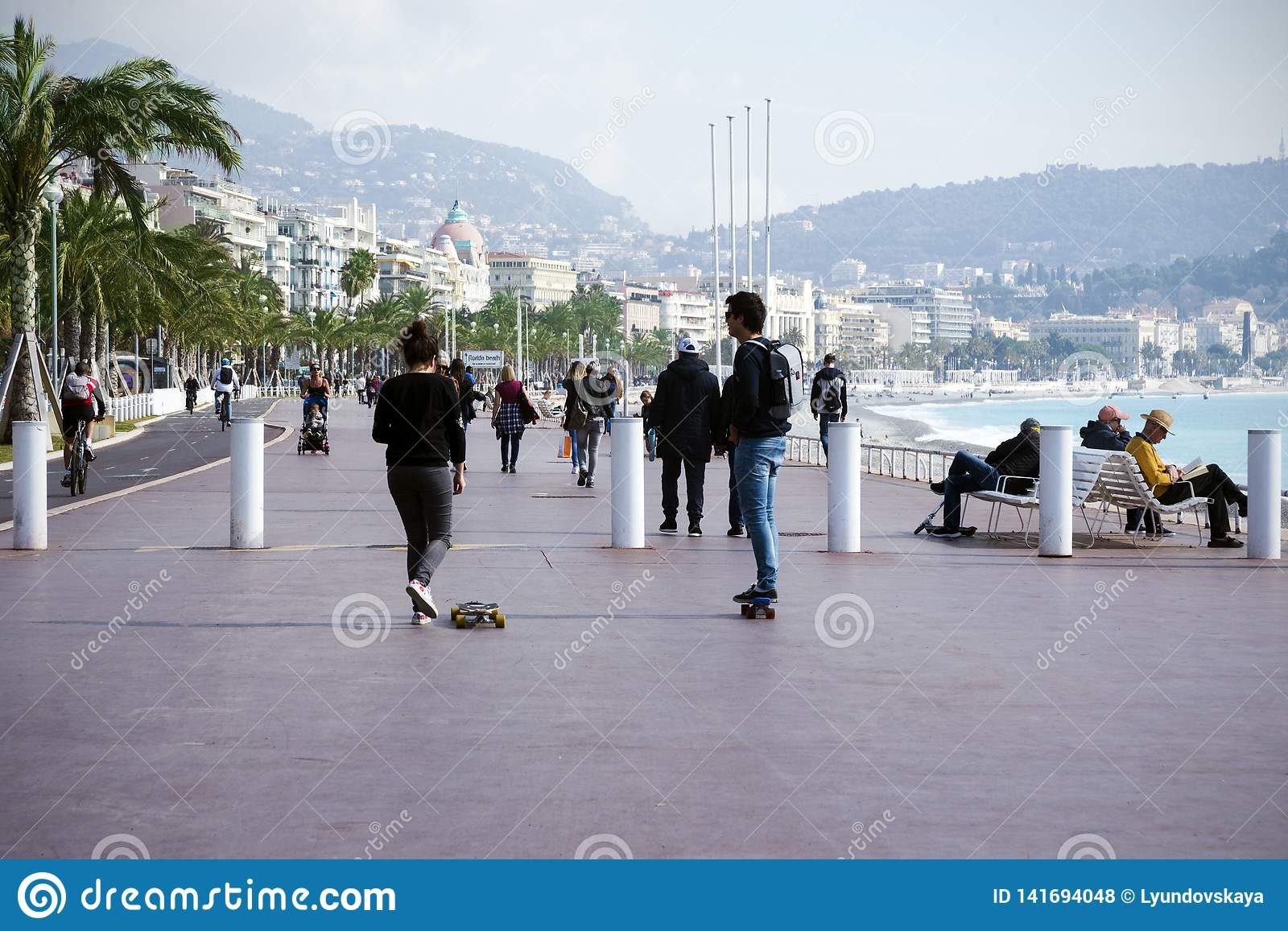 Nice, France, March 2019. Two young people: a boy and a girl ride a skateboard along the promenade. Cote d`Azur.