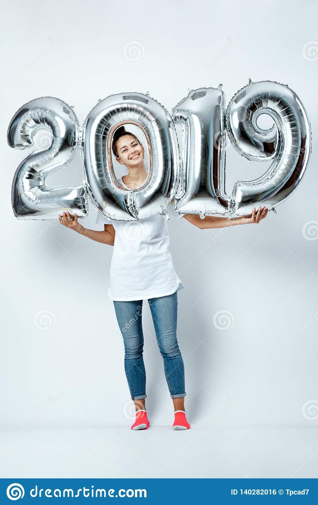 Nice funny girl dressed in white t-shirt, jeans and pink socks holding balloons in the shape of numbers 2019 on the
