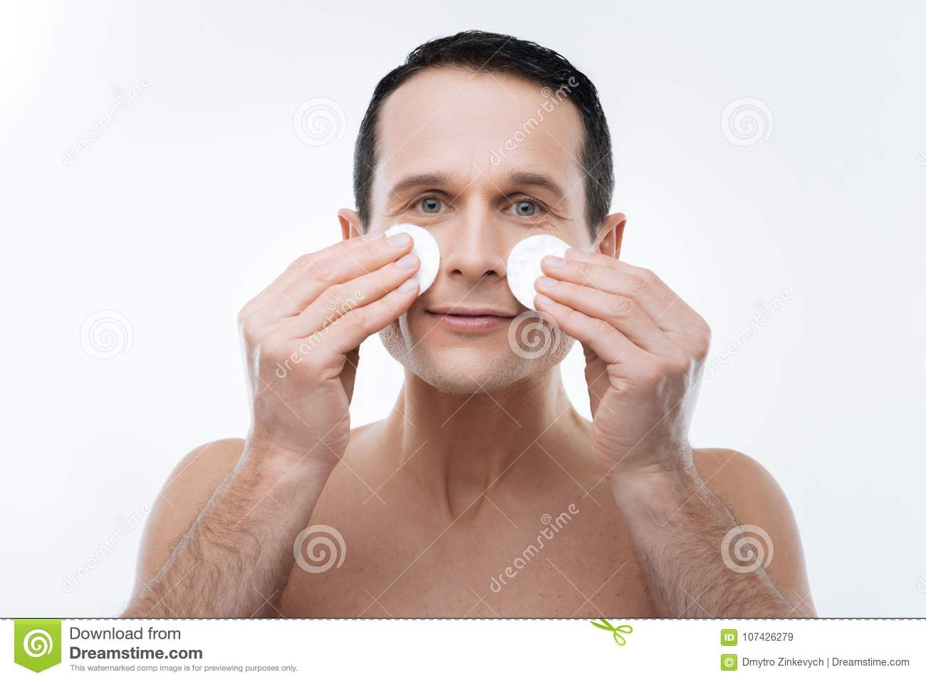 Nice handsome man holding cotton pads