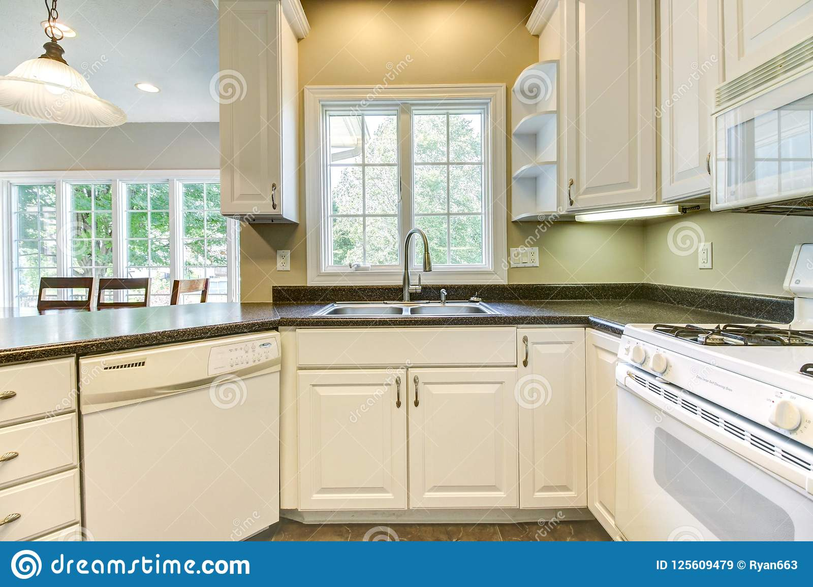 Nice Kitchen With White Cabinets And Black Countertops ...