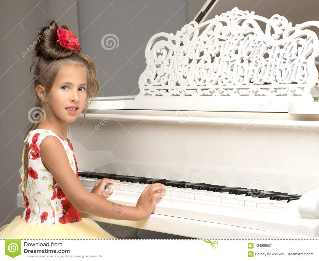 Beautiful Little Girl Is Playing On A White Grand Piano
