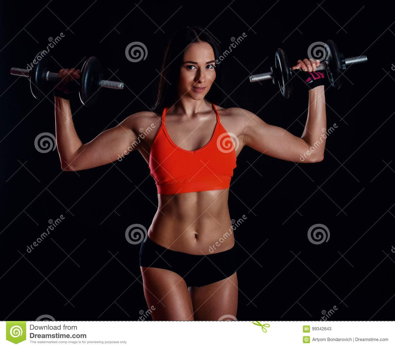 Nice girl doing workout with dumbbells isolated over black background. Athletic young woman do a fitness workout with weights