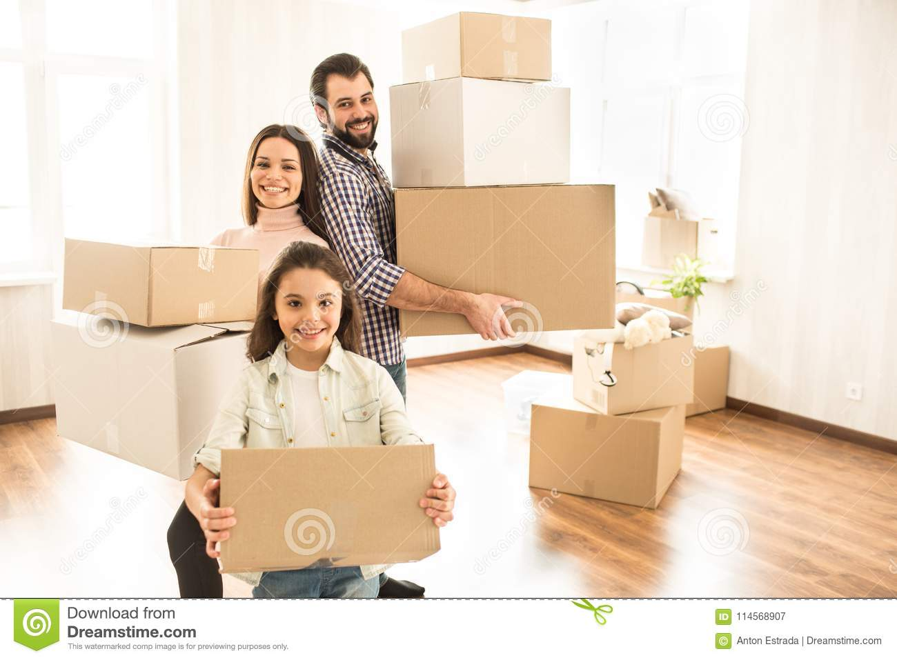 Nice shot of two parents and happy child holding boxes and looking to the camera. They are standing very close to each