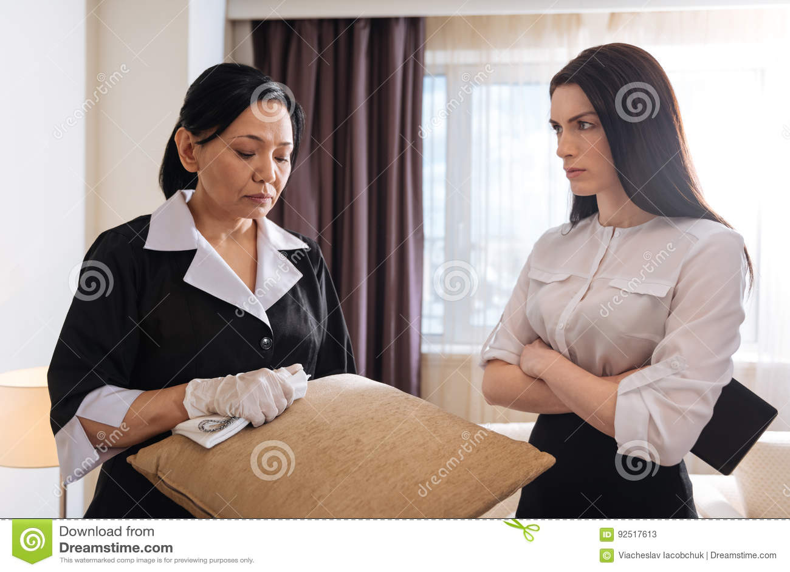 Nice unhappy hotel maid holding a cushion