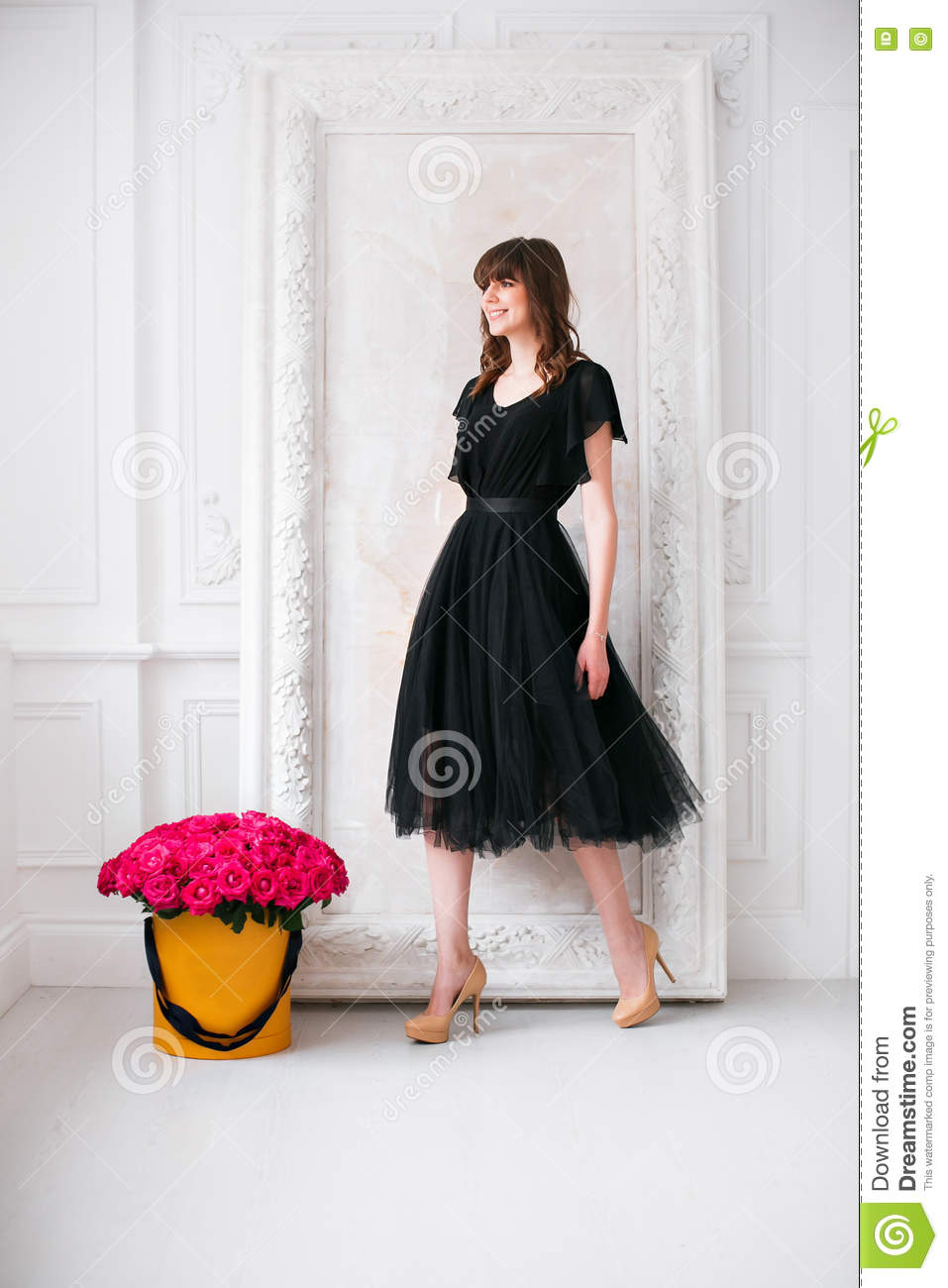 Nice young blonde girl. in a black dress and shoes on high heels. smelling flowers holding purple roses bouquet in hat
