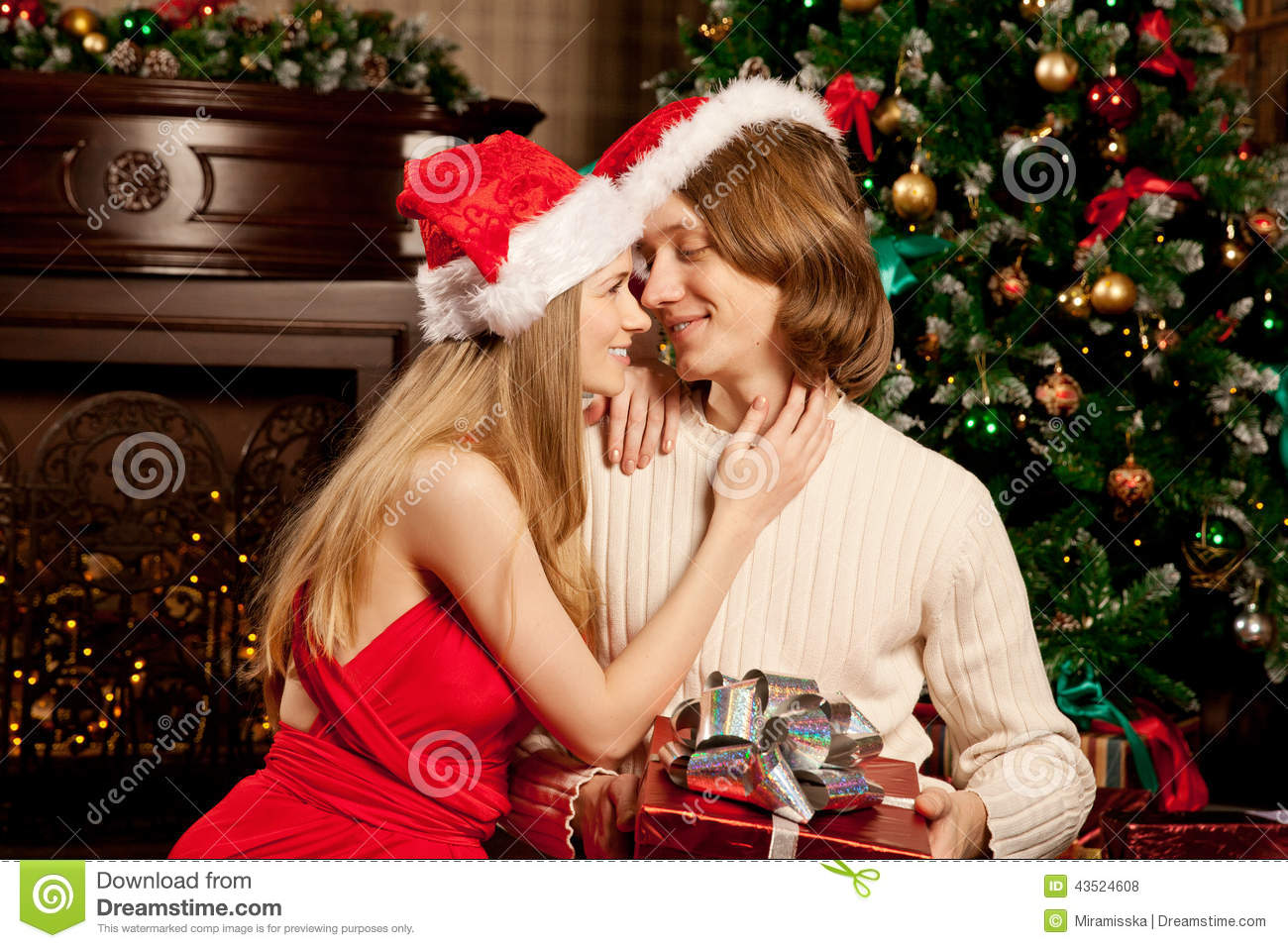 Nice Young Love Couple Near The Christmas Tree. Woman And Man Ce ...