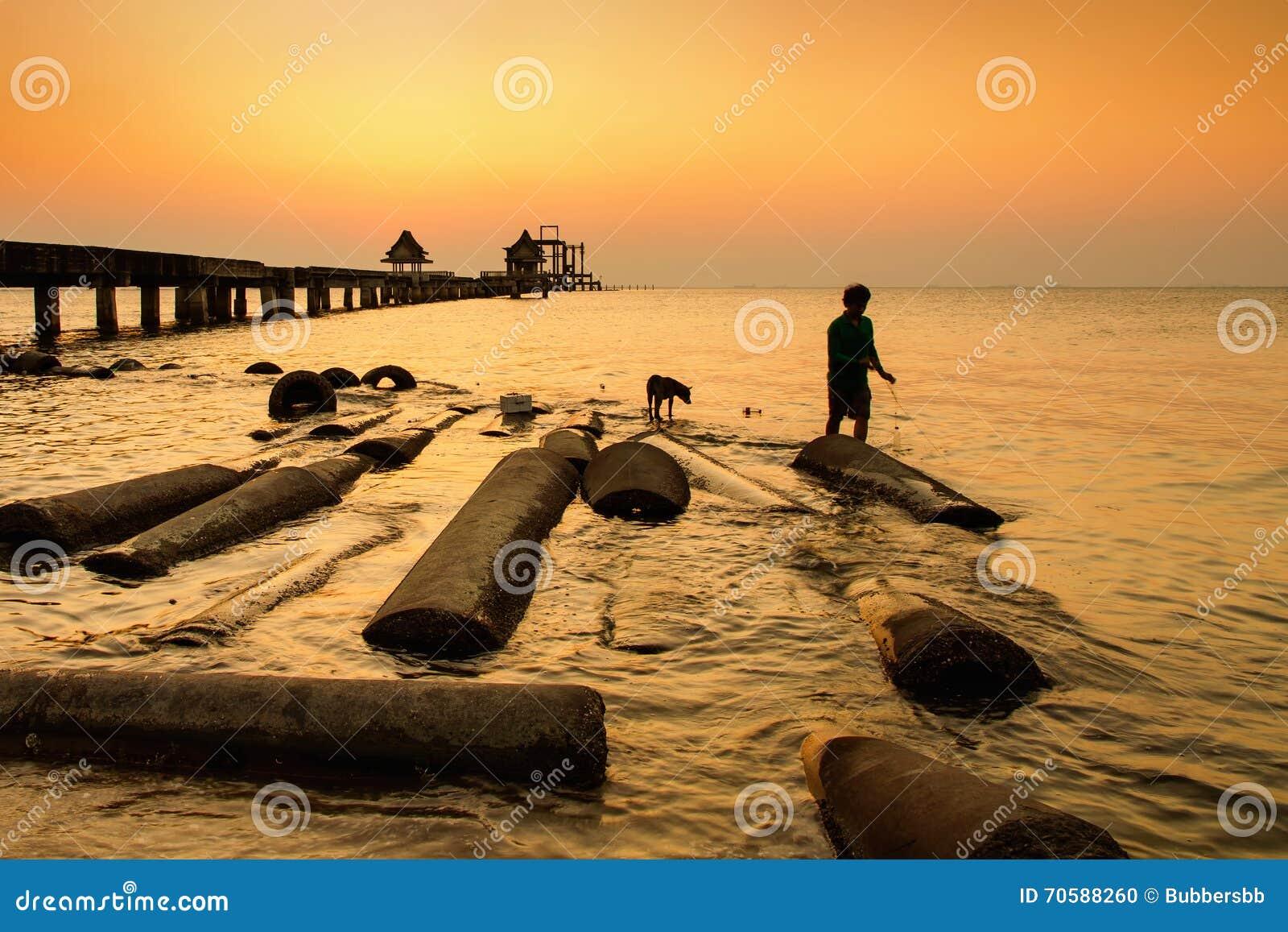 Nicht identifiziertes Fischer- und Hundefischen an der Brücke im Sonnenuntergang thailand