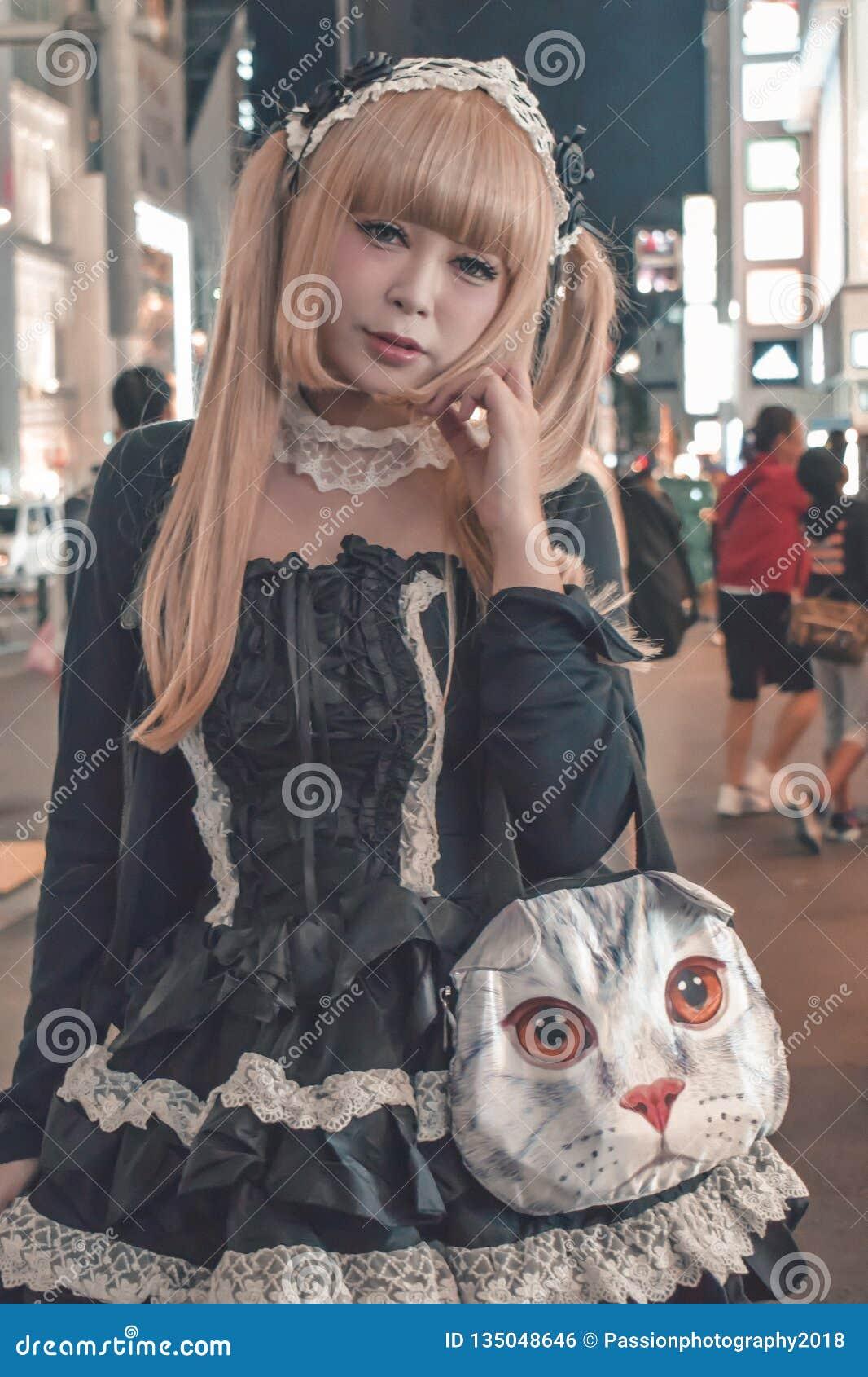 Nicht identifiziertes japanisches Mädchen mit dem blonden Tauchhaar mit einer katzenähnlichen Handtasche bei Harajuku in Beispiel