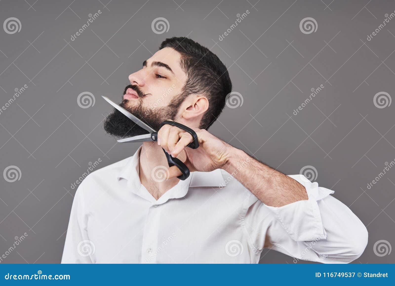 Nicht mehr Bart Porträt des hübschen jungen Mannes, der seinen Bart mit Scheren schneidet und Kamera bei der Stellung betrachtet