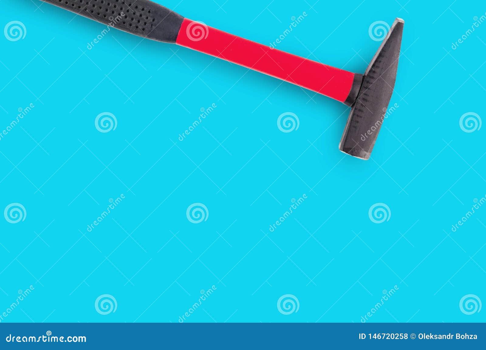 ?nico martelo do metal com o punho de borracha vermelho e preto no fundo azul