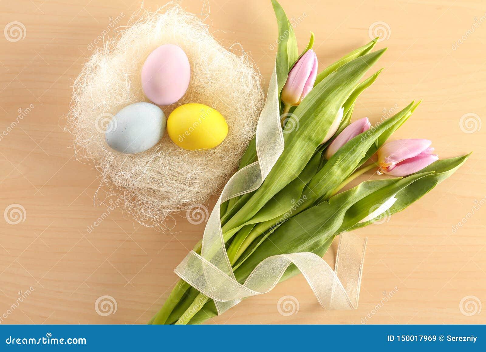 Nid décoratif avec les oeufs de pâques et les fleurs teints de ressort sur la table