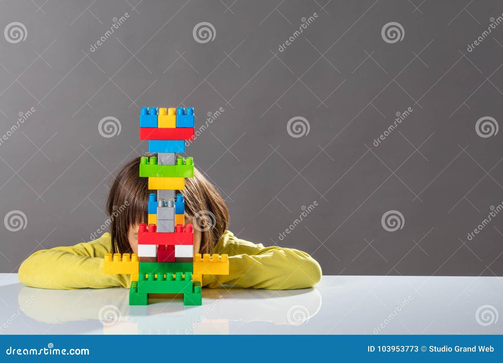 Nieśmiały małe dziecko chuje za budującą zabawką dla dzieciak psychologii