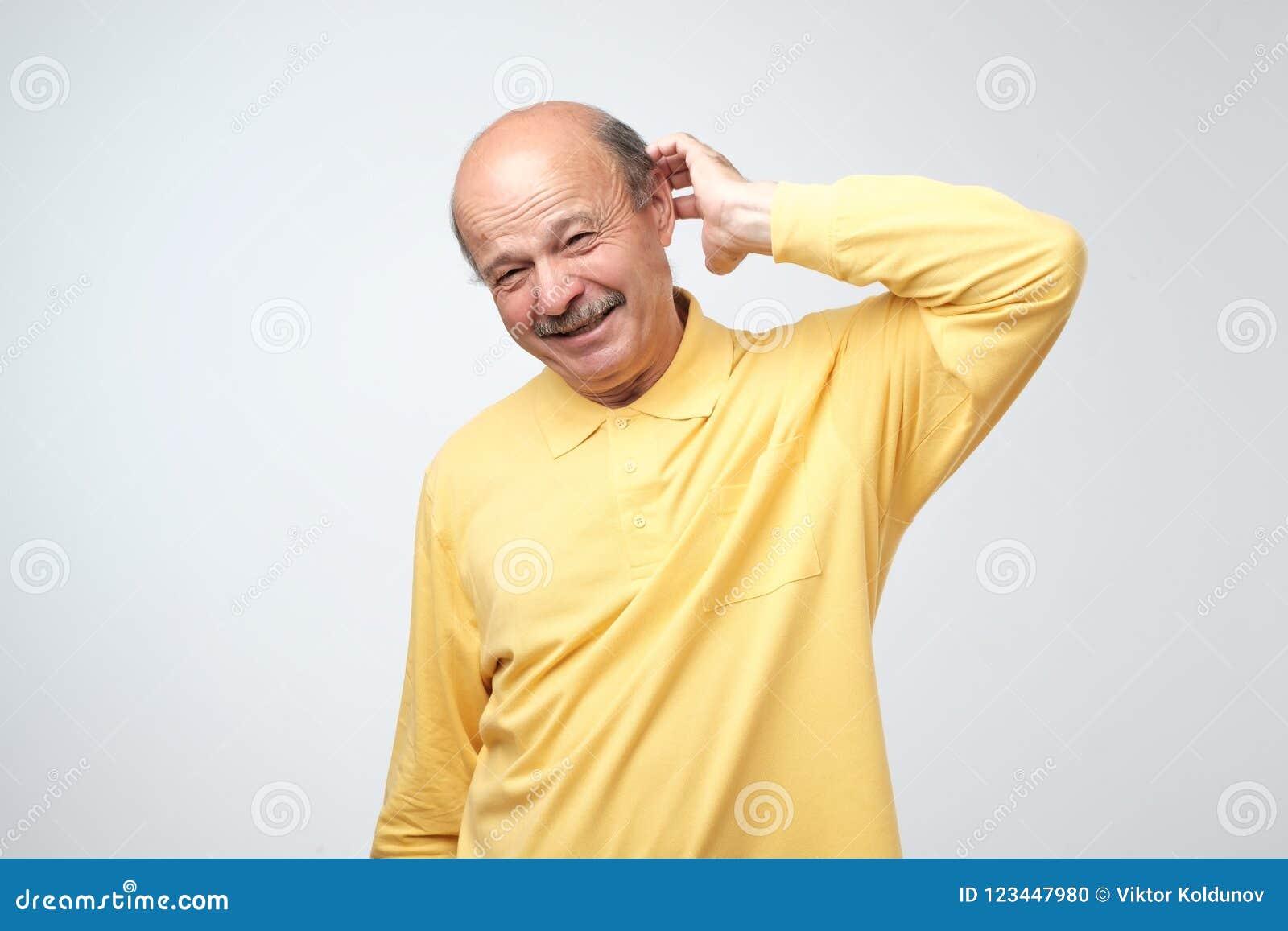 Nie pewny Dojrzały dorosły w żółtej tshirt havinga wątpliwości
