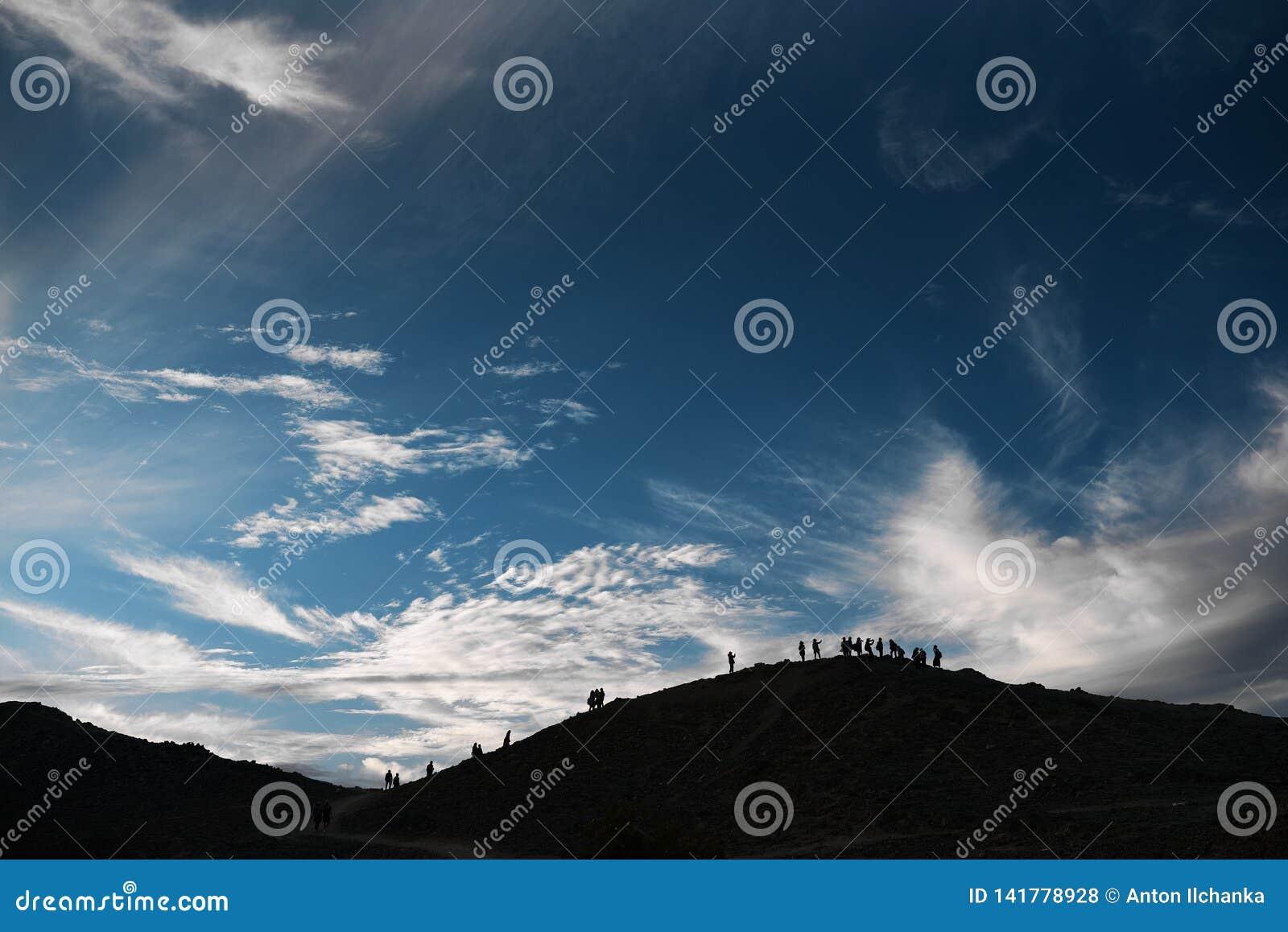 Niebieskie niebo z chmury wzgórza górami z konturami ludzie