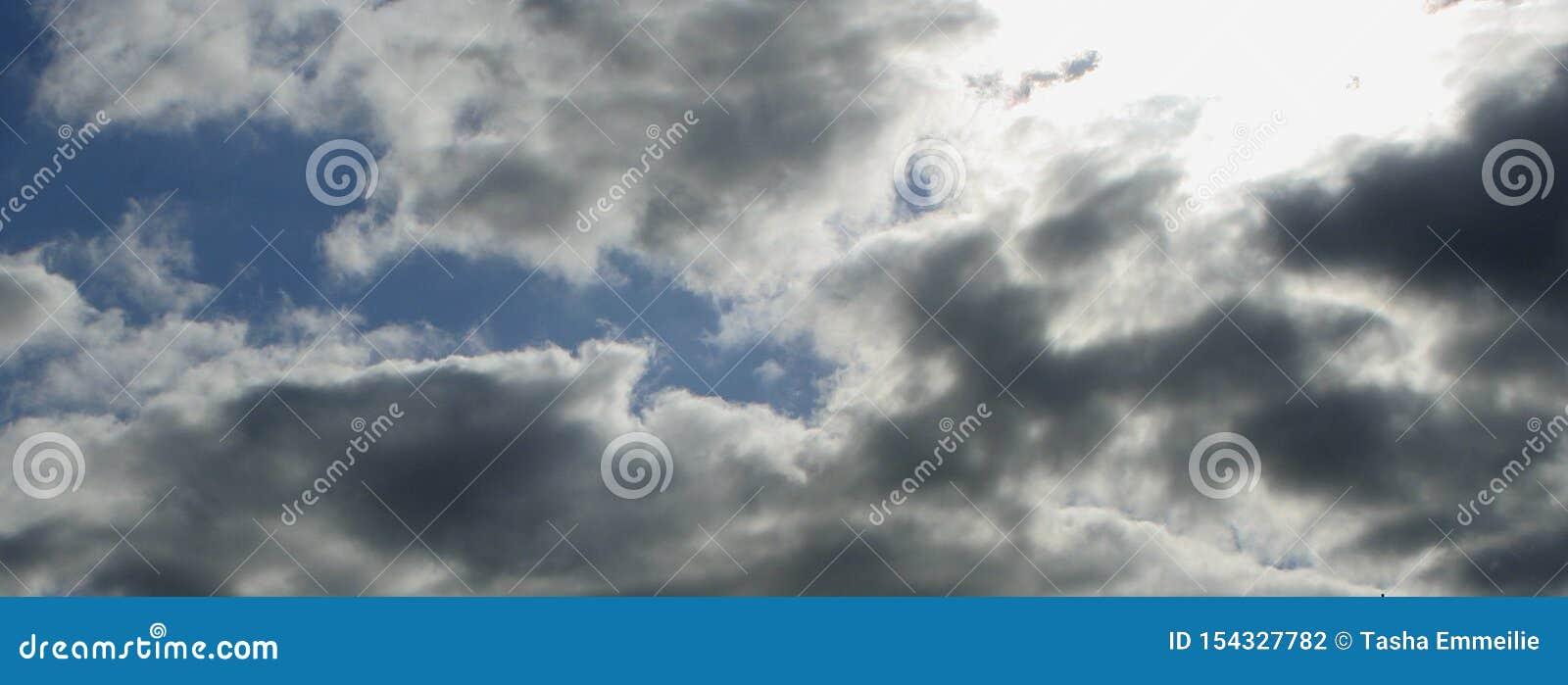 Niebieskie niebo z puszystymi białymi i popielatymi chmurami, słońca jaśnienie