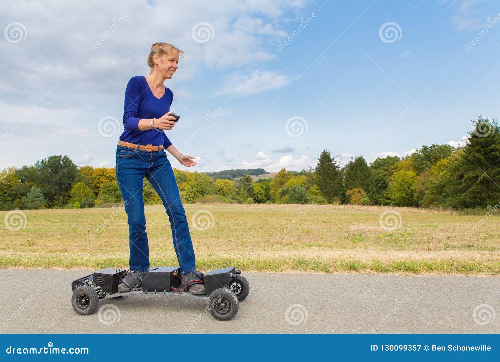 Niederländische Frau fährt elektrisches mountainboard in der Natur