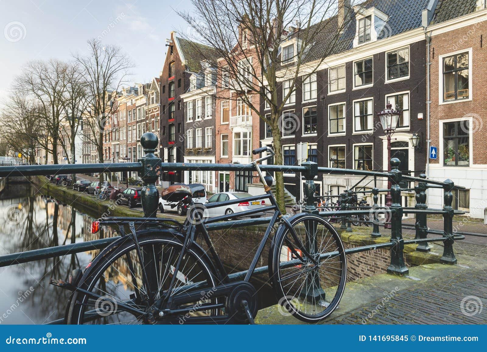 Niederländische Kanalhäuser mit dem Fahrrad, das an der Brücke sich lehnt