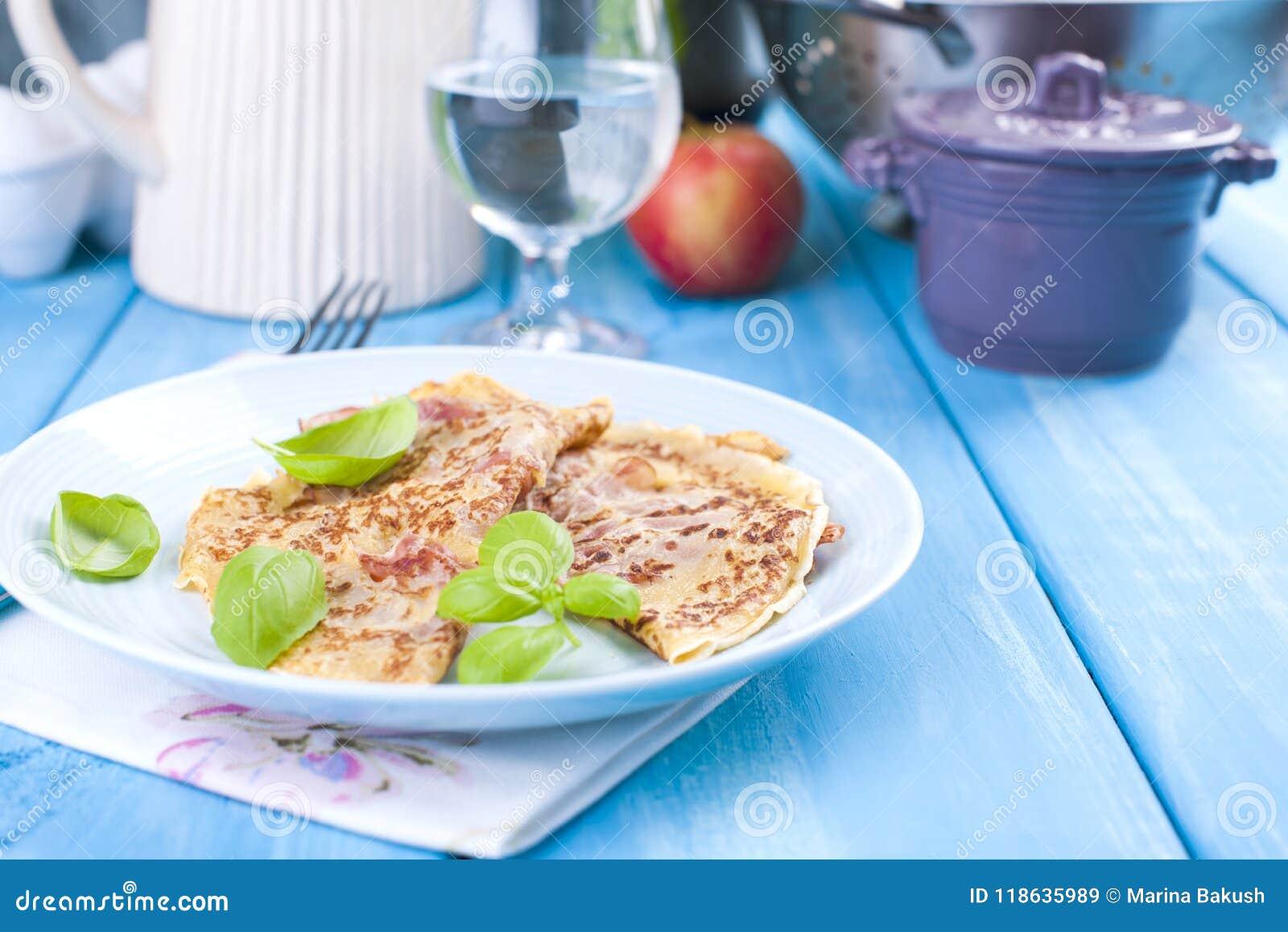 Niederländische Pfannkuchen mit Schinken für helle Farben des Frühstücks, blauer Hintergrund Geschmackvoll und kalorisch Glas Was