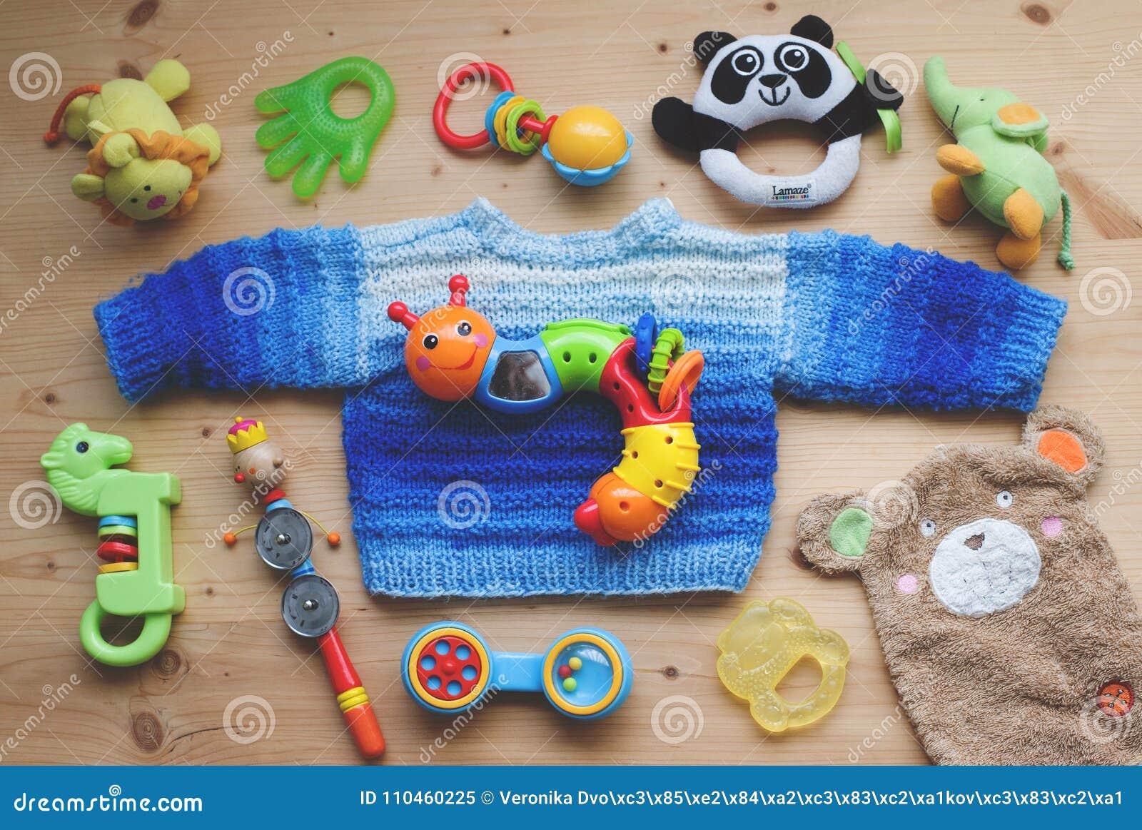 Niederstetten Tyskland, Februari 2018: Barnleksakerna och den hemlagade blåa tröjan som ligger på träbakgrund