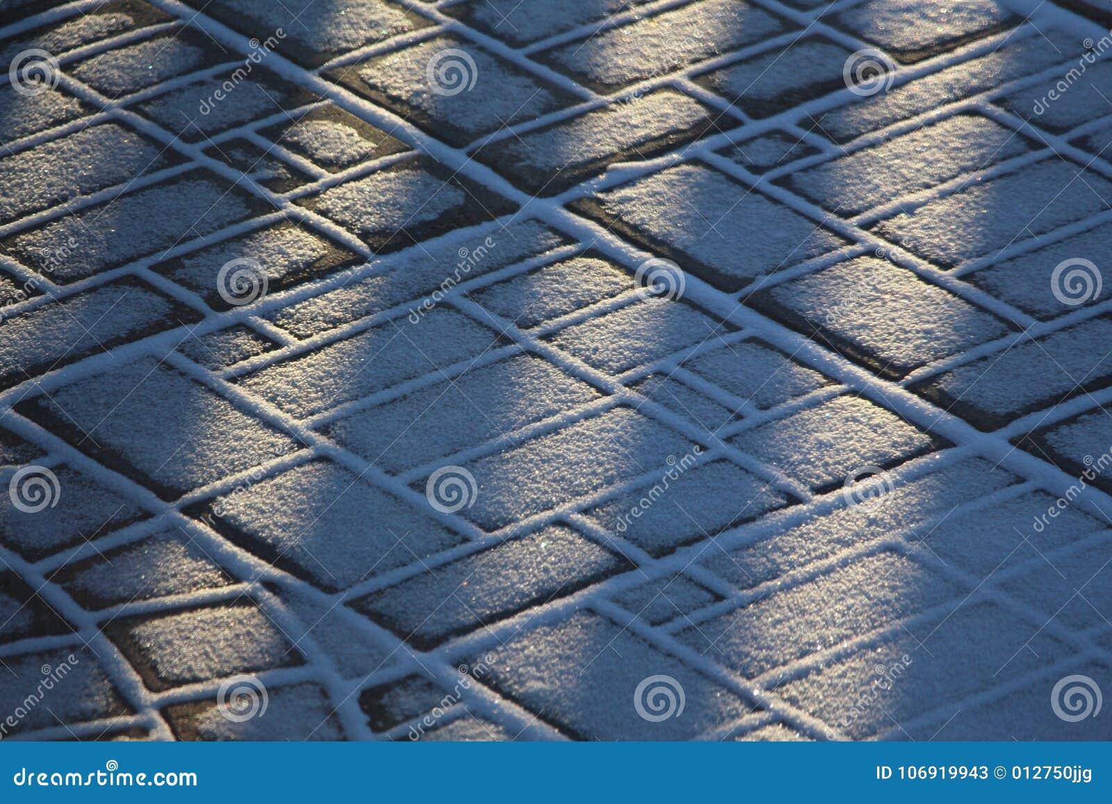 Śnieg tekstury na brukowych kamieniach i wzory