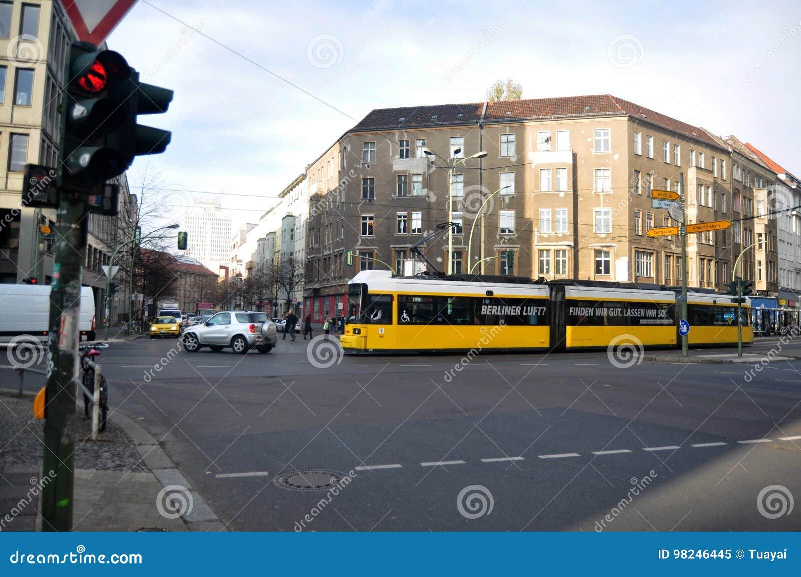 Niemieccy ludzie chodzi przy złączem i prowadnikowy samochód na drodze z tramwajarskimi sieciami