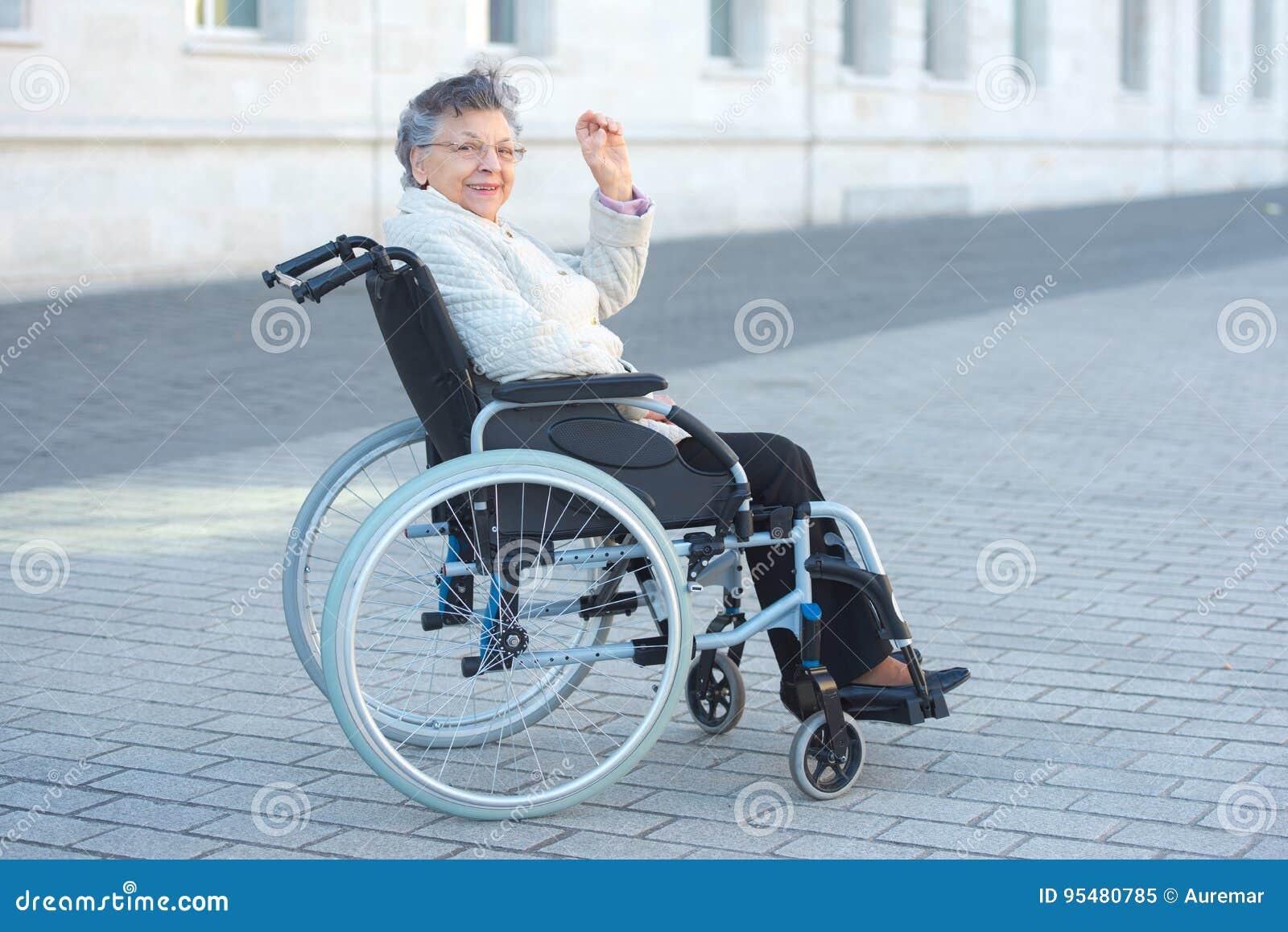 Niepełnosprawnej kobiety siedzący outside i falowanie