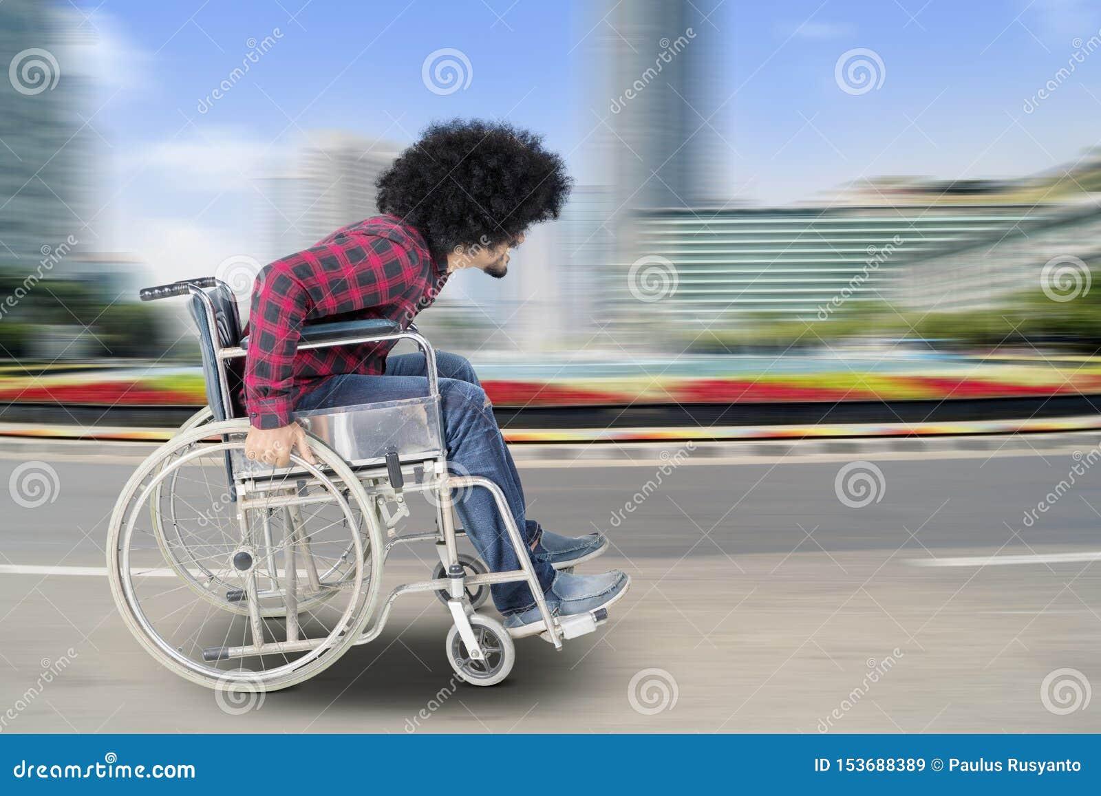 Niepełnosprawny mężczyzna siedzi w wózku inwalidzkim z szybkim ruchem