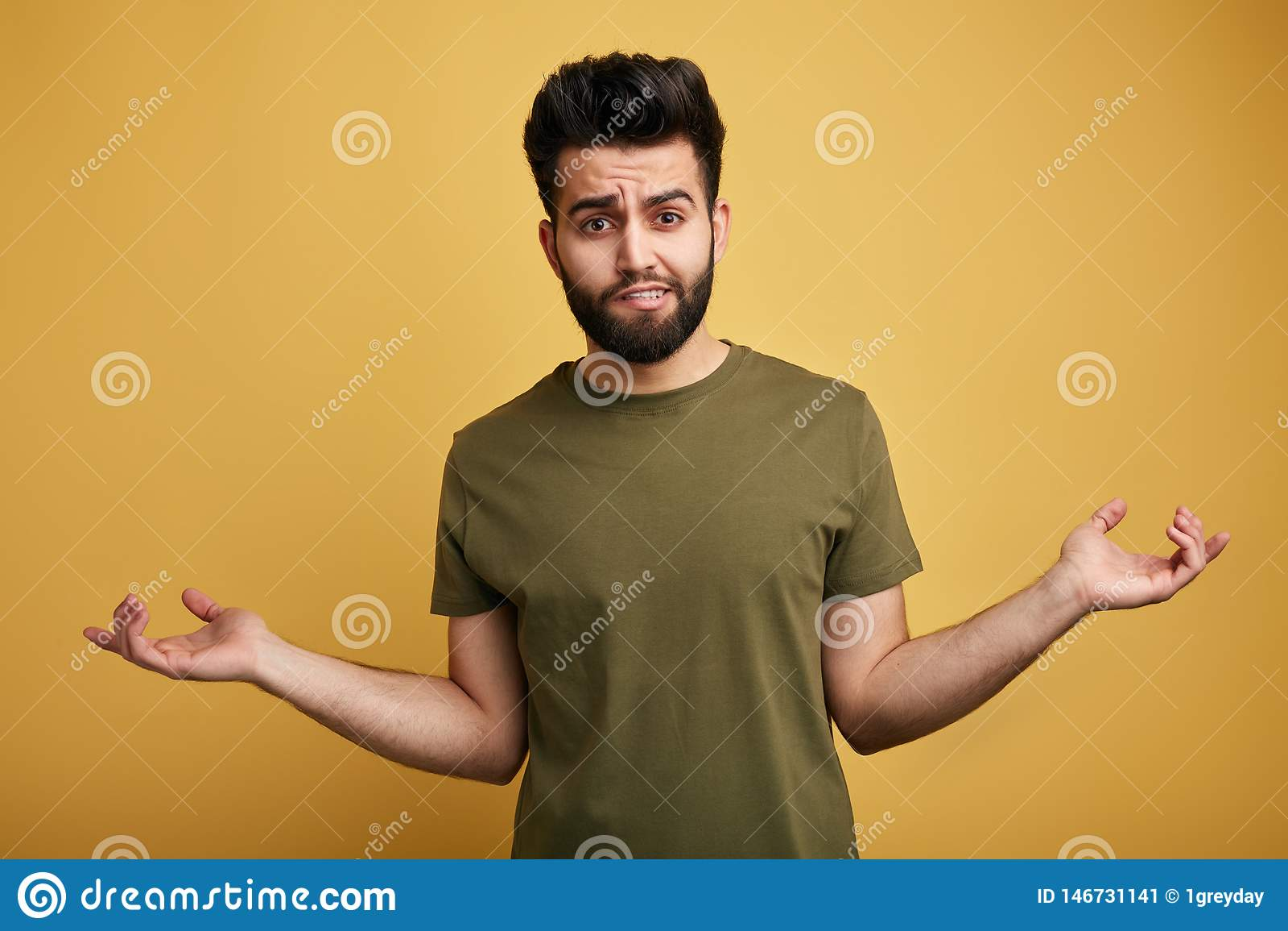 Niepewny wątpliwy brodaty mężczyzna jest ubranym zieloną koszulkę wzrusza ramionami jego brać na swoje barki