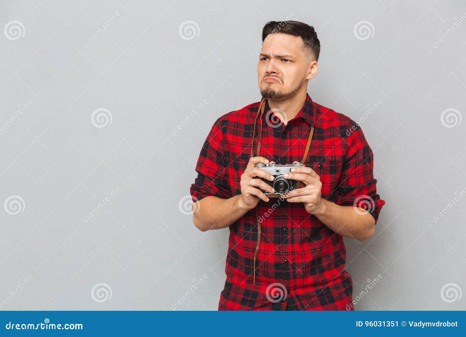 Nierad mężczyzna w koszulowego mienia retro kamerze