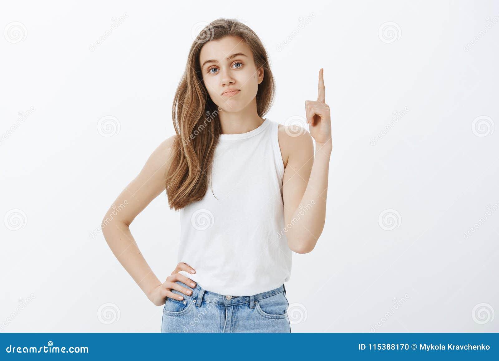 Nierada nieporuszona atrakcyjna kobieta z uczciwym włosy trzyma rękę na biodrze, pokazuje liczbę jeden i podnosi wskaźnika,