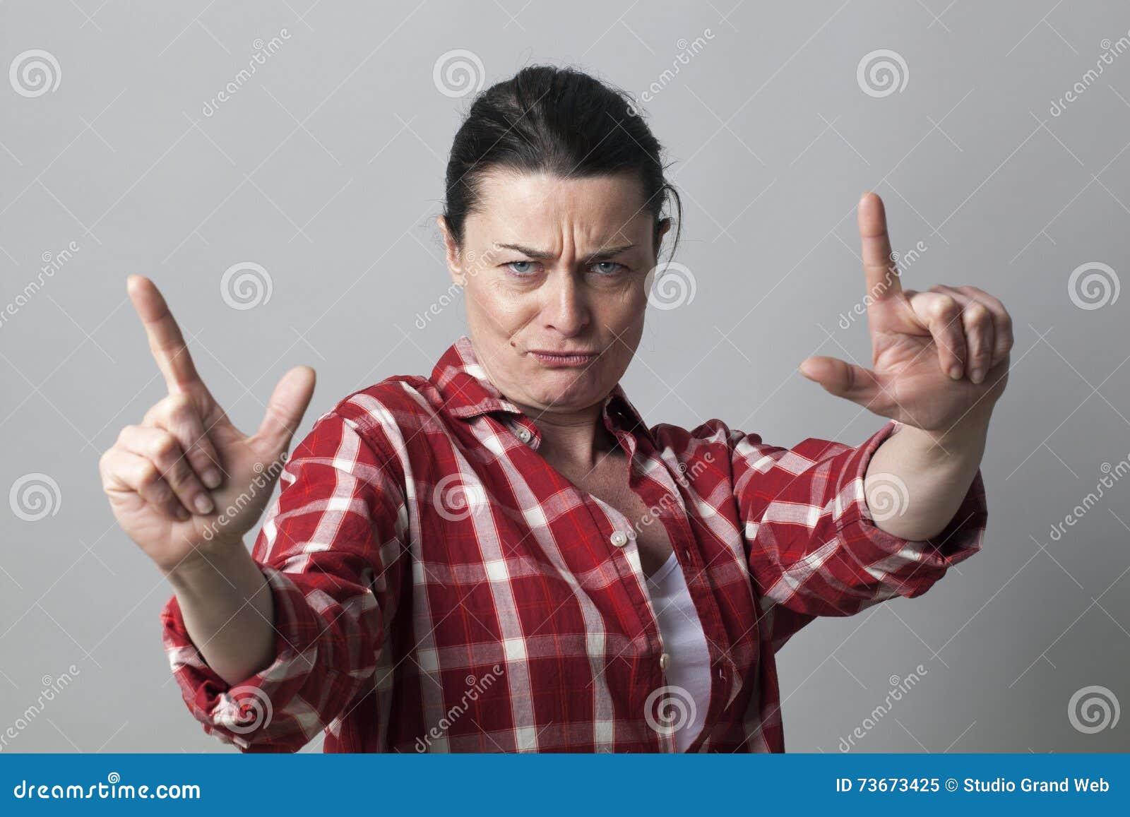 Nierada w średnim wieku kobieta pokazuje agresywnego ręka gest