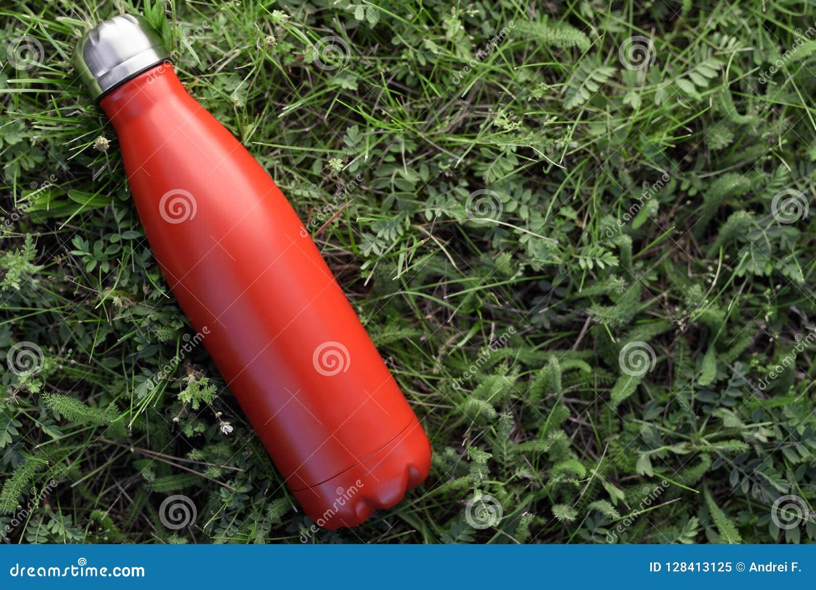 Nierdzewny butelka termos, czerwony kolor Na zielonej trawy tle